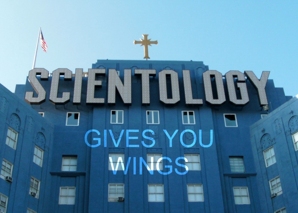 A picture of Scientology's Pacific Area Command Base, a large blue building in Los Angeles affectionately known as 'Big Blue.' The words from Red Bull's famous slogan, 'Gives You Wings,' have been edited in below the building's large 'Scientology' sign.