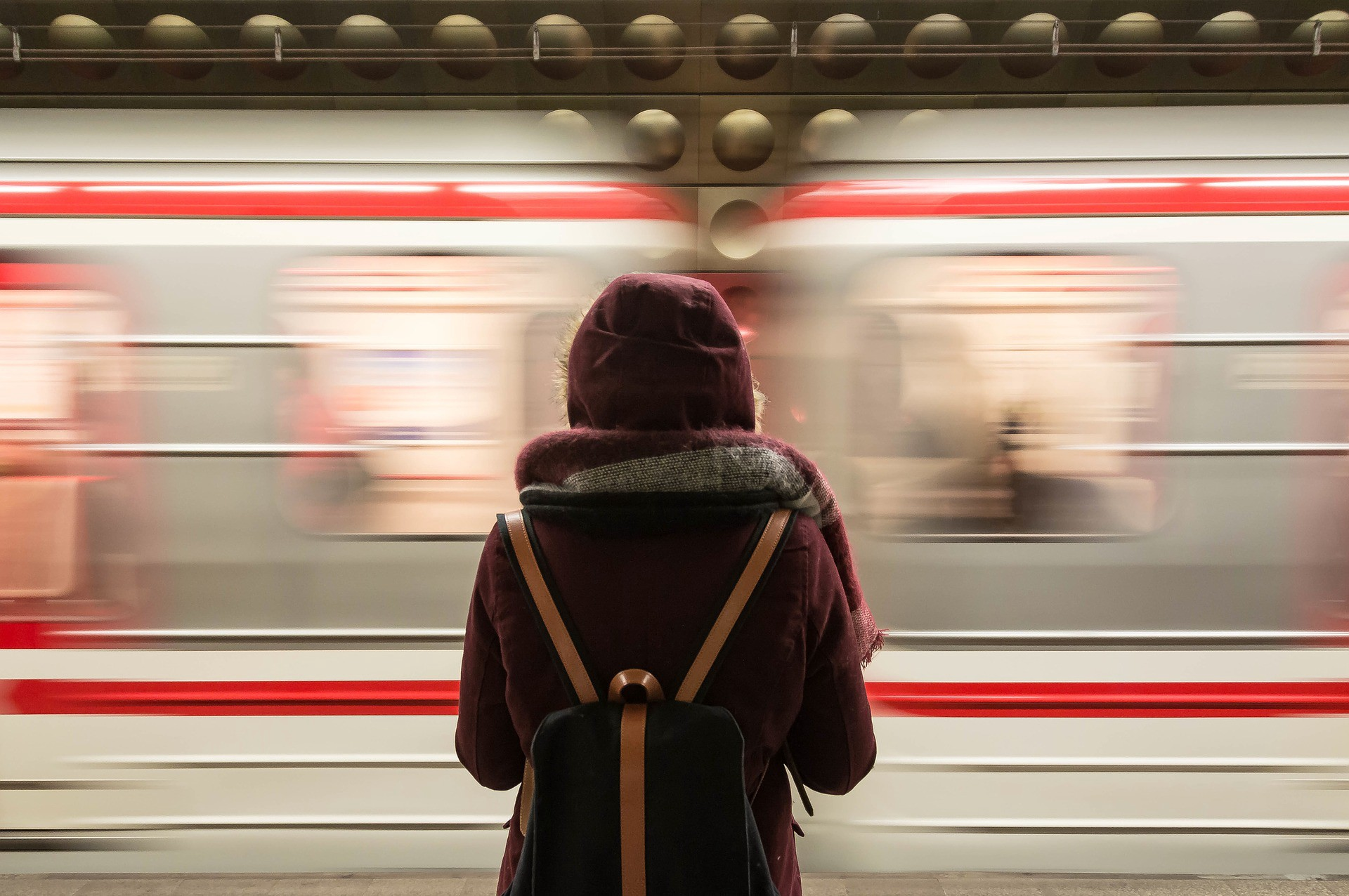 Well lit photo of the back of a person in deep red winter coat with hood up as a train passes in front of them at a station.
