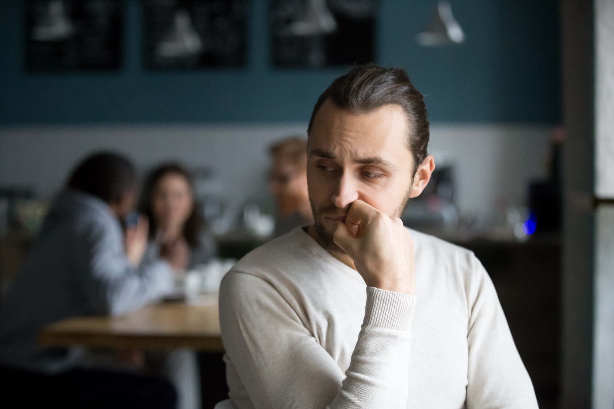 A white man sits alone in a cafe. He faces the camera, but his attention is on a group behind him he wants to be a part of.