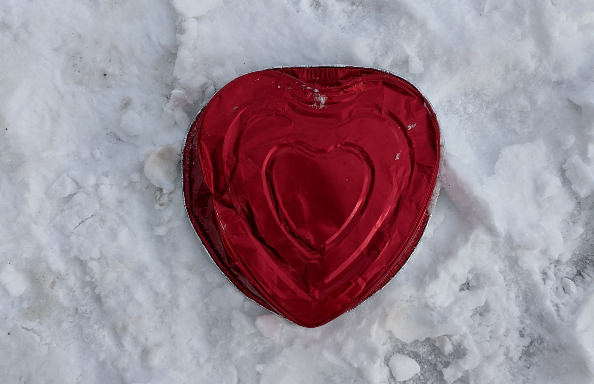 a valentine's day heart tin laying in snow