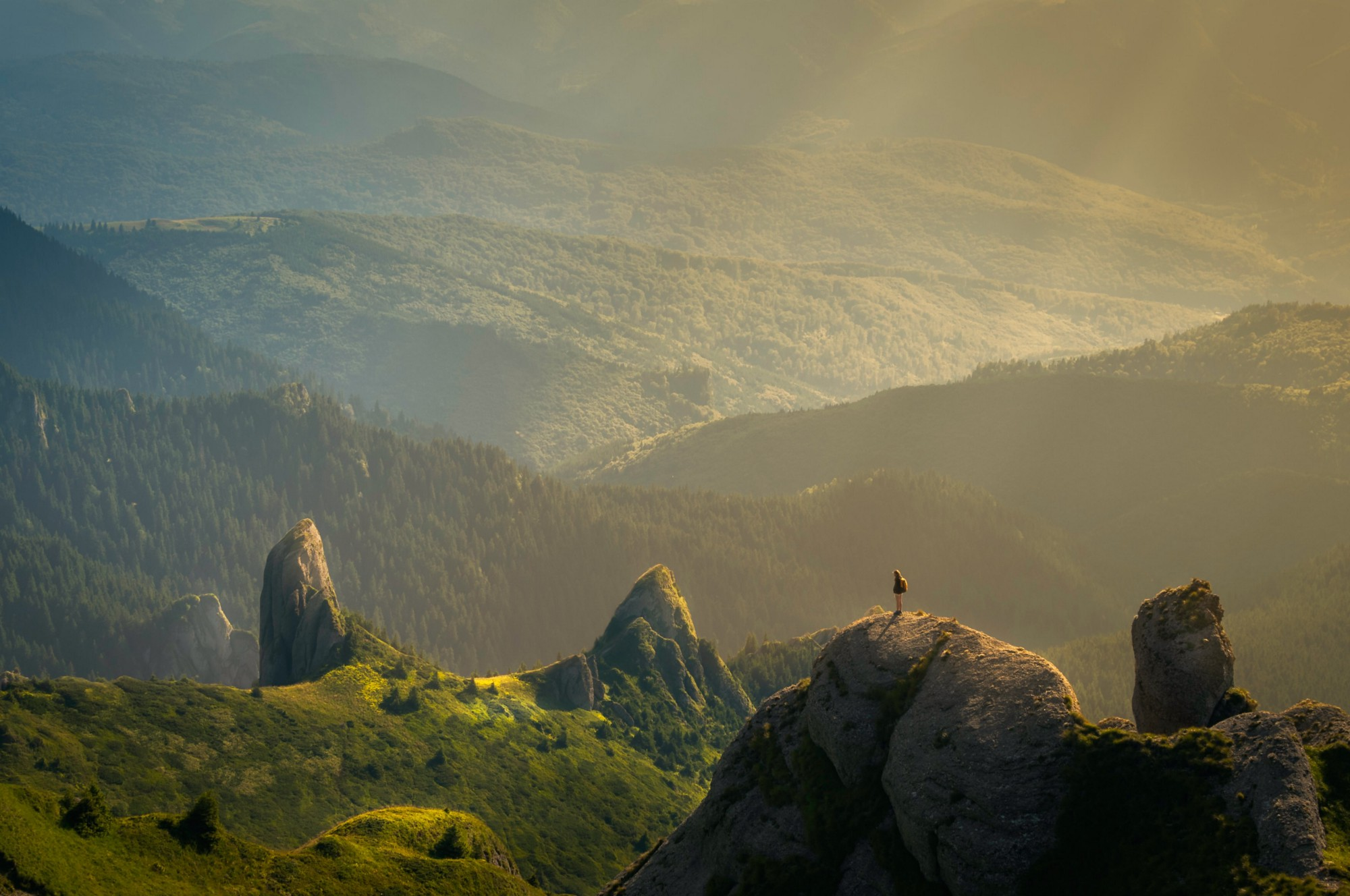 person walking across mountaintops