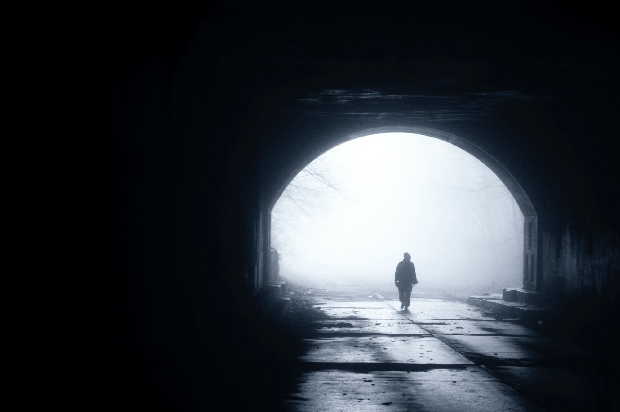 A dark tunnel, with a distant burst of sunshine framing a distant individual walking towards us.