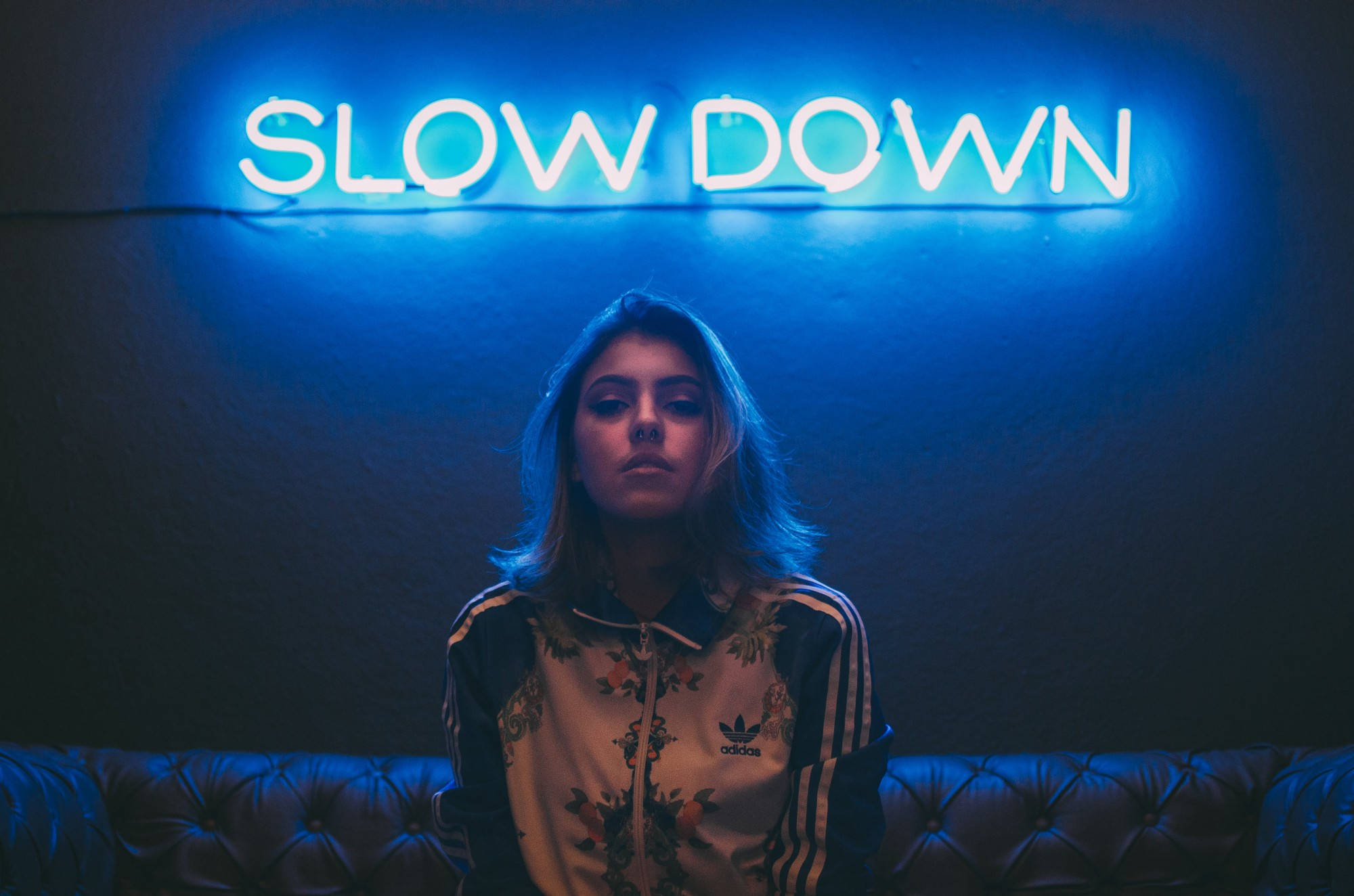 """A woman sits underneath a neon sign reading """"slow down>'"""
