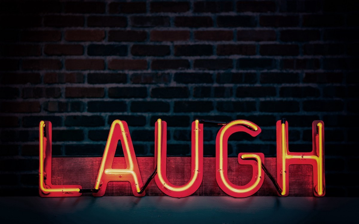 """A red neon sign reading """"LAUGH"""" against a dark brick background"""