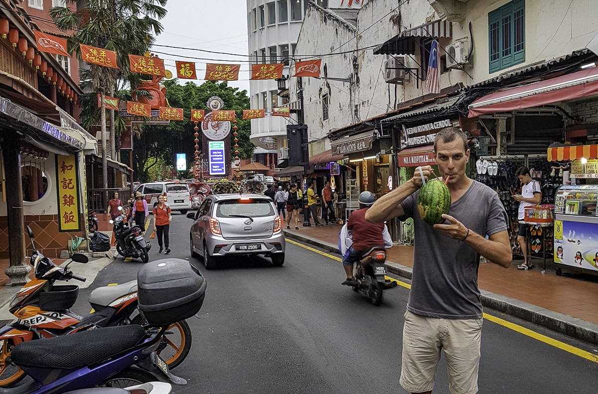 Matt Hallowes drinking out of a watermelon in Melaka, Malaysia