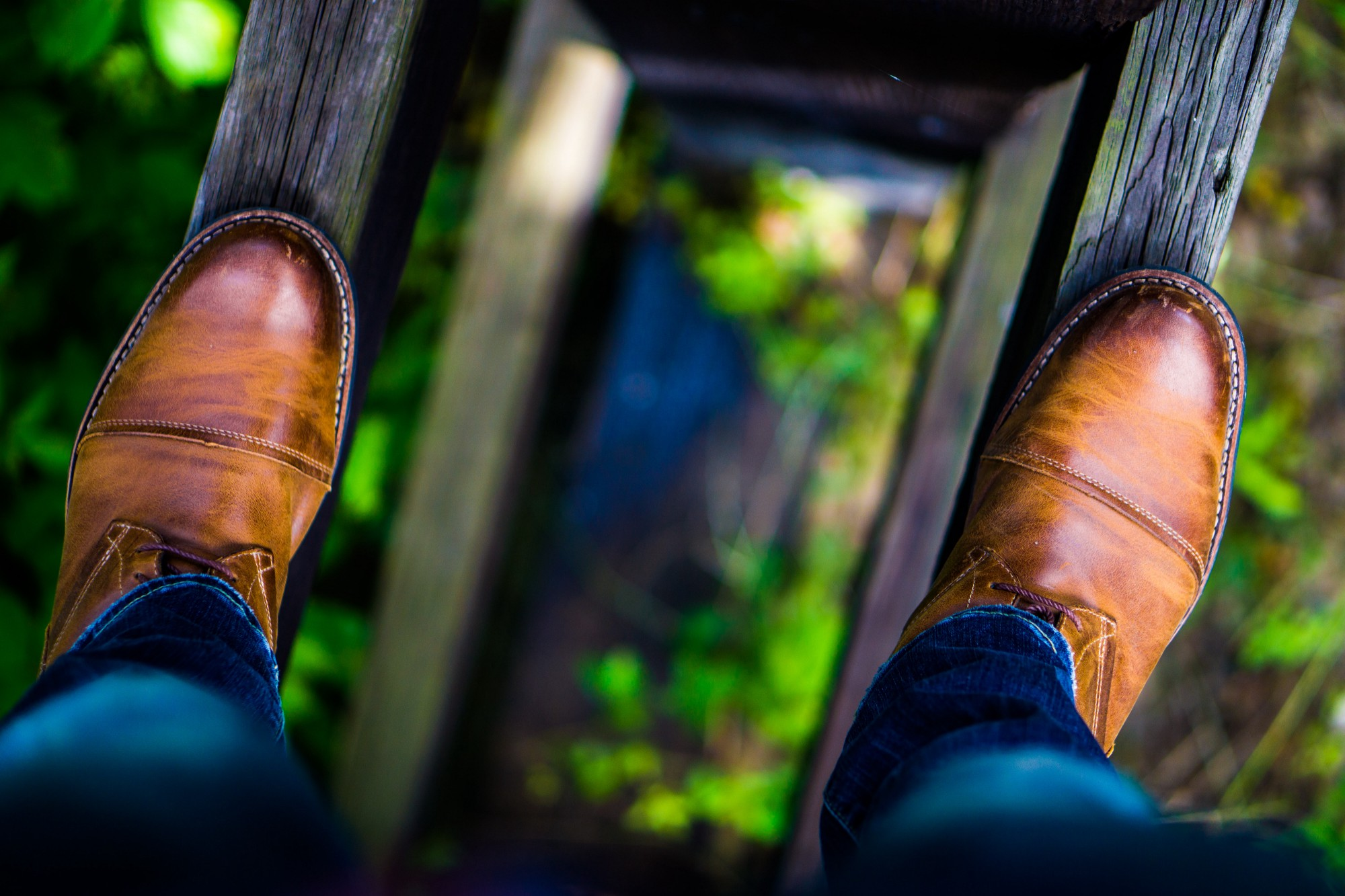 Image of a man's legs and dress shoes balanced on wood beams over a forest