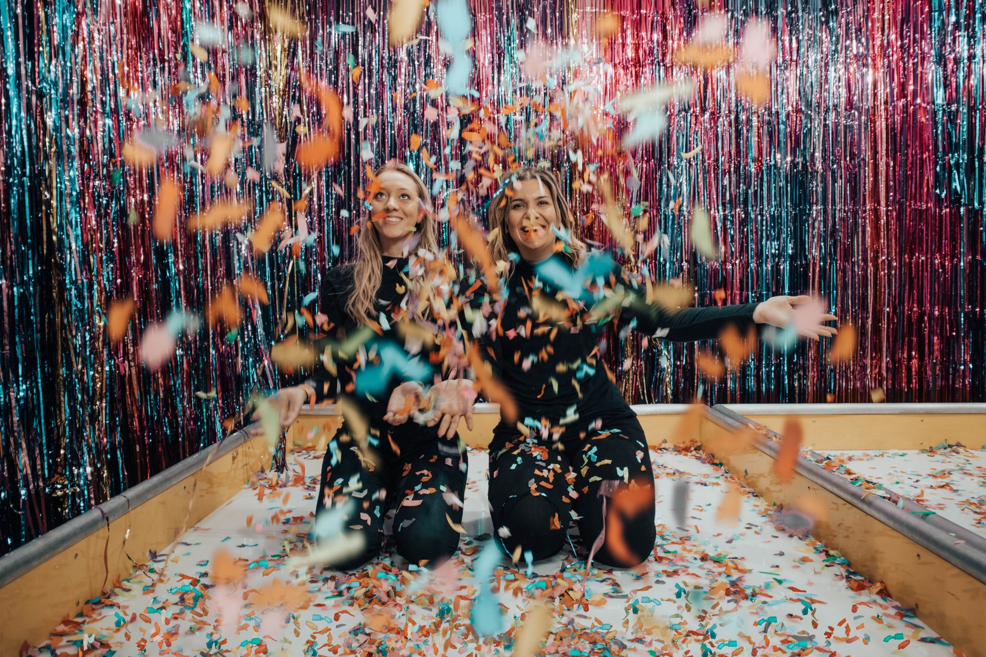 Two girls playing around with confetti.