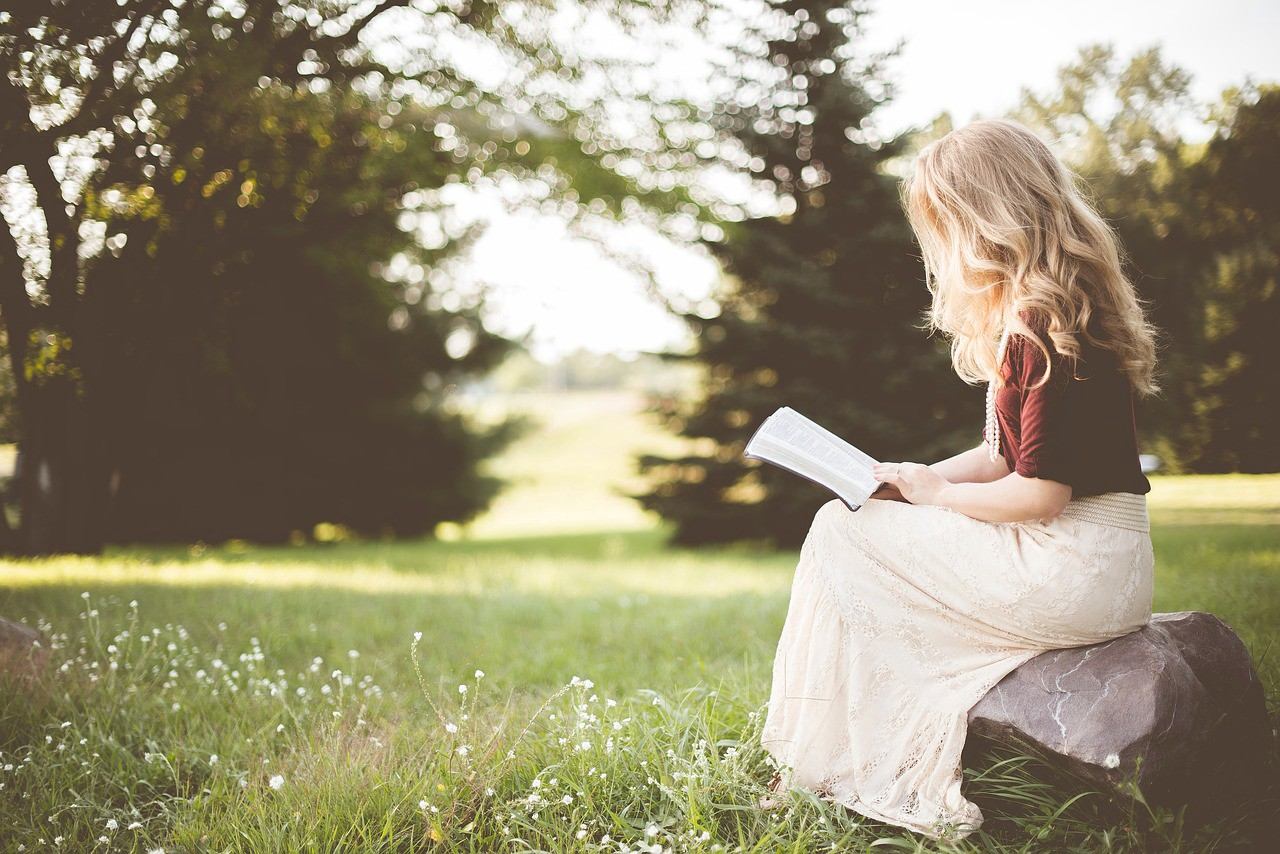 A blonde woman sitting on a rock in a park, reading a book