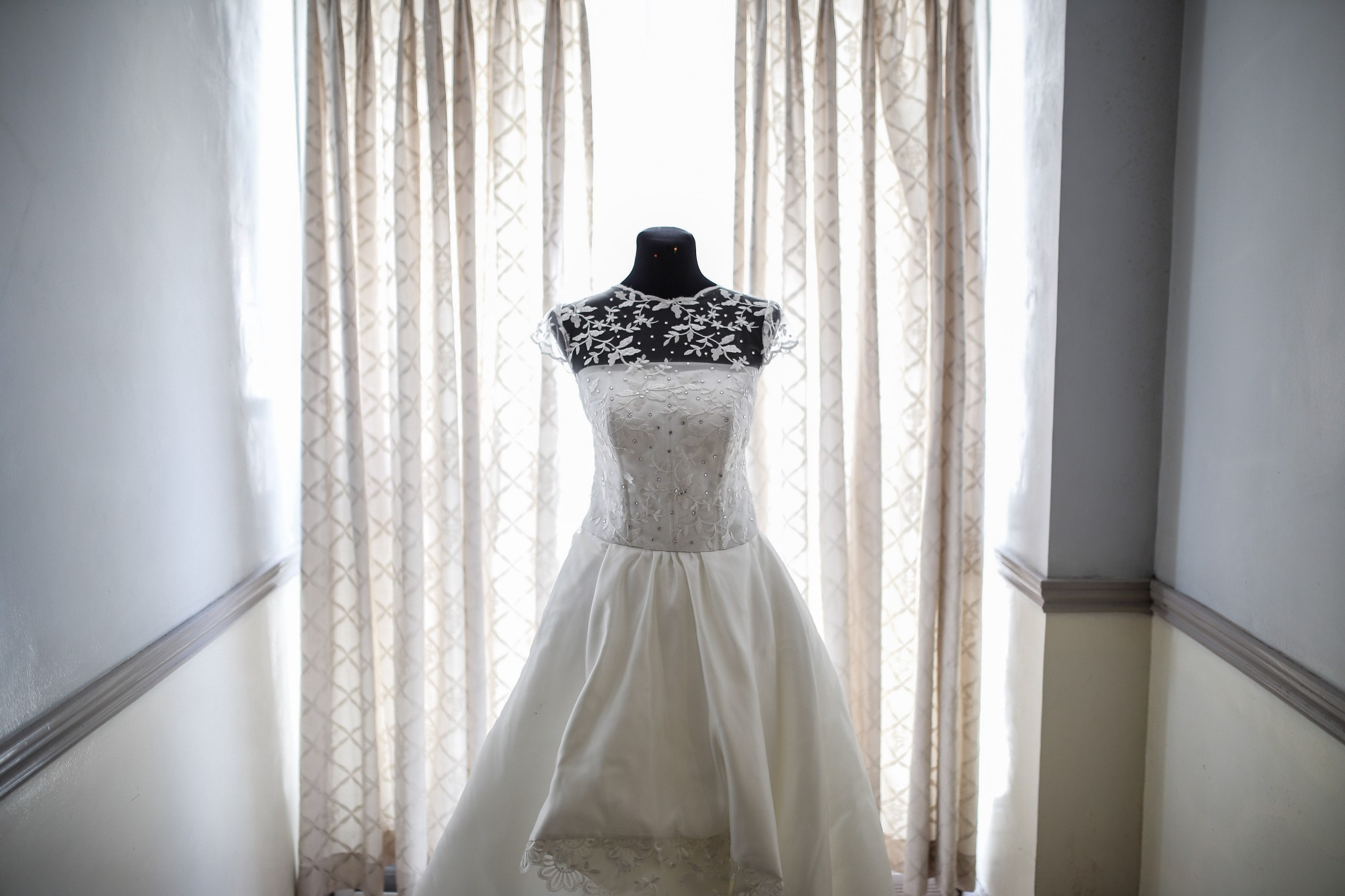 A wedding dress hanging up in a bedroom in front of a window.
