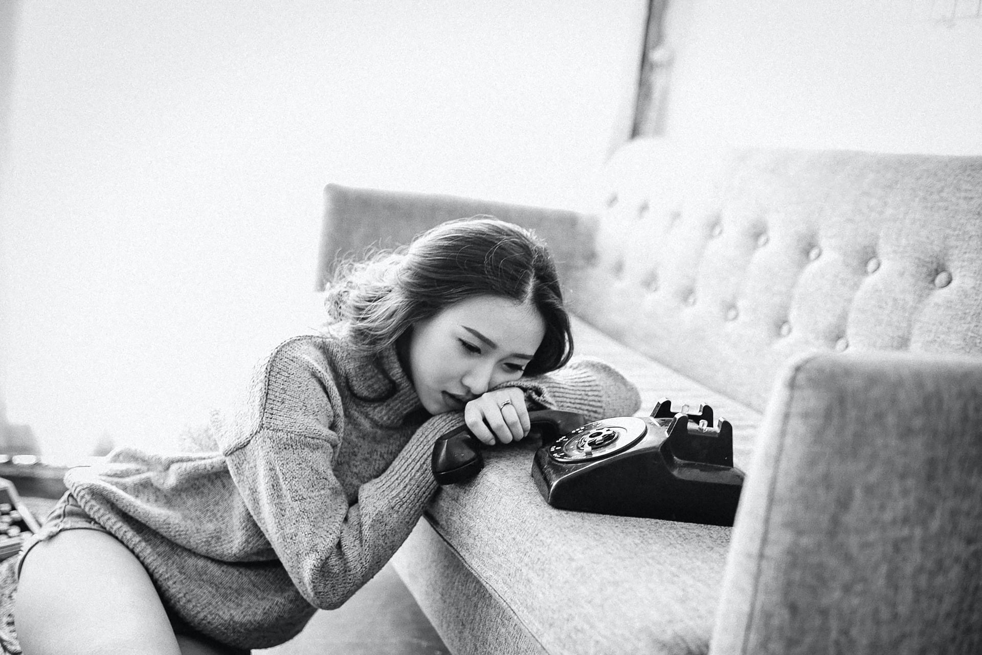 Black and white picture. Sad woman staring at an oldschool phone, the handset in her hand.