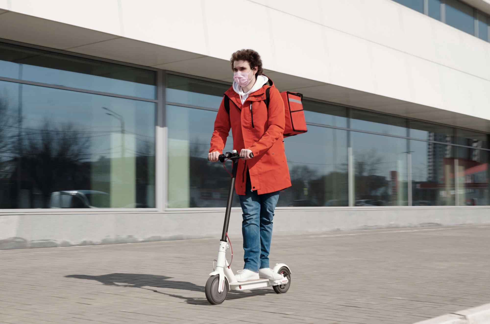 A masked delivery worker rides an electric scooter past a building.