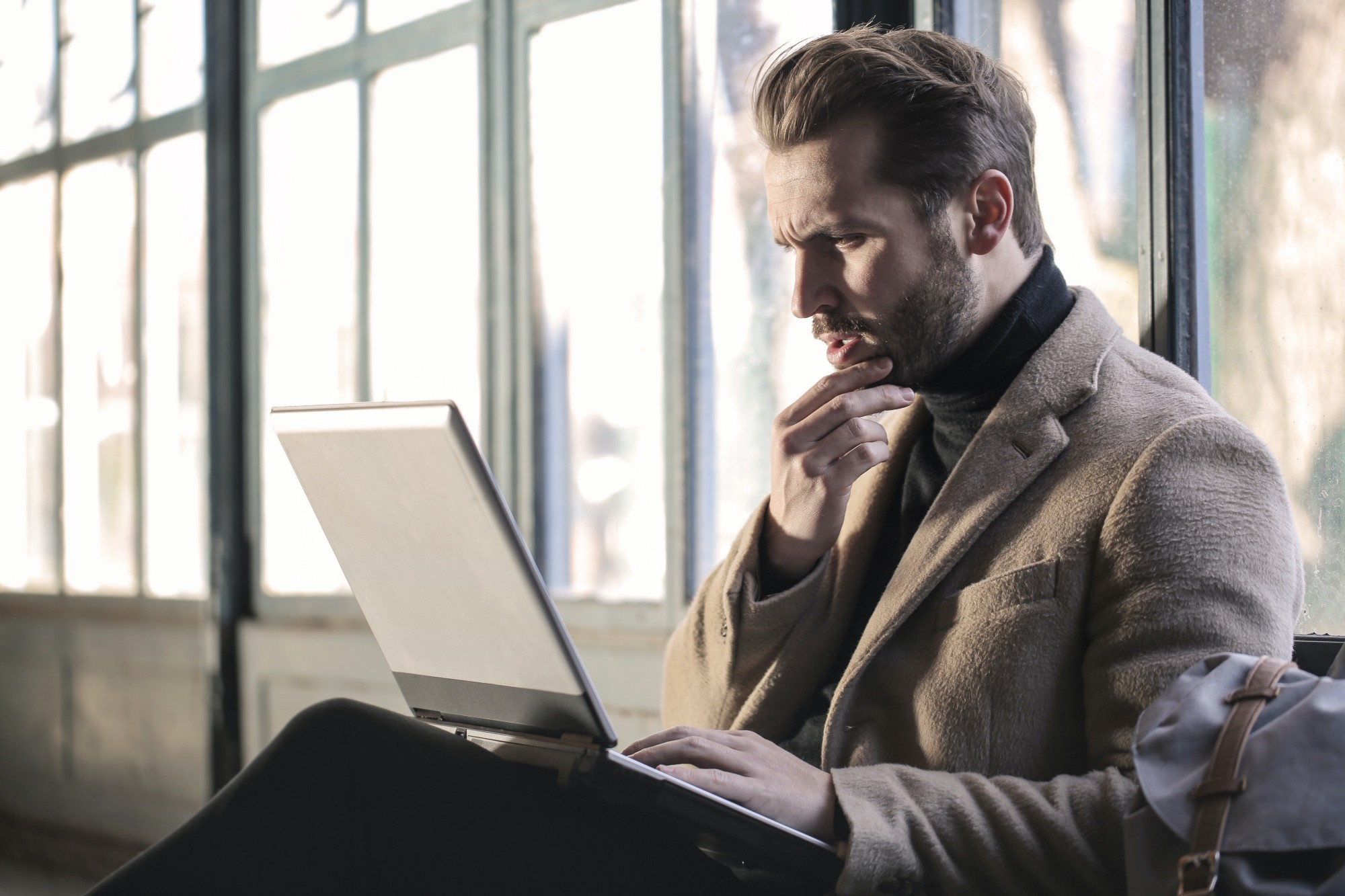 Man sitting with laptop staring pensively at the laptop screen.