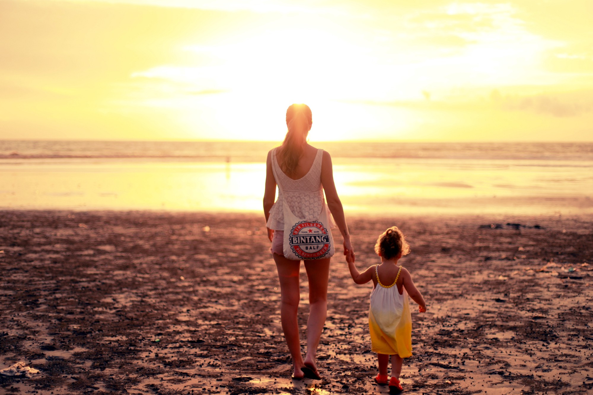 Photo of a grown up woman and a child walking on a beach towards the sun