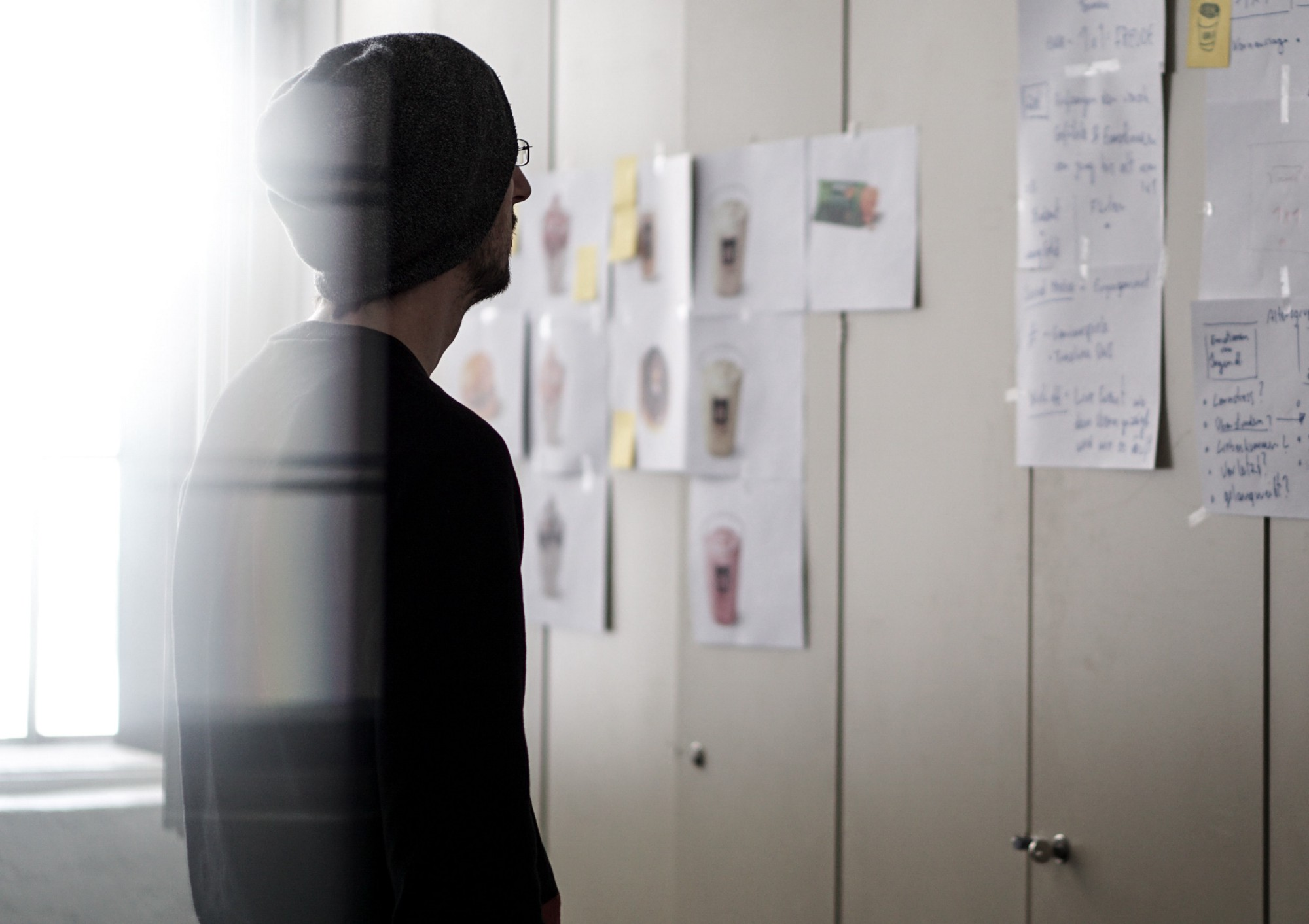 a man looking at the wall full of notes and post-its. Image taken from Unsplash