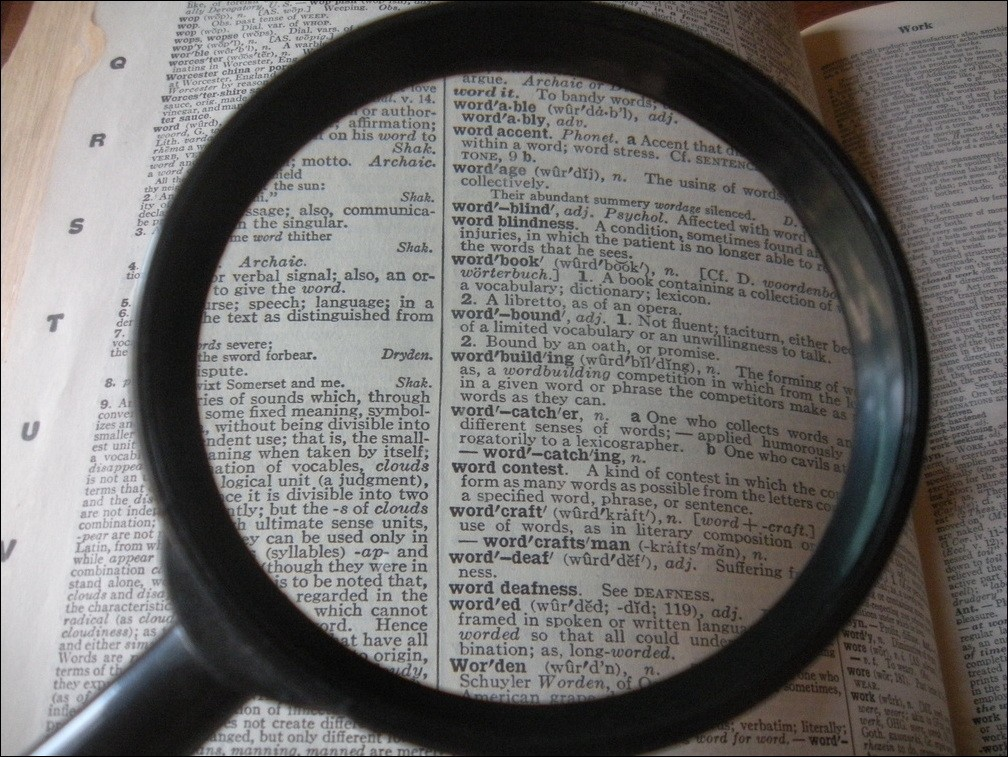 A magnifying glass focusing on a page in the dictionary