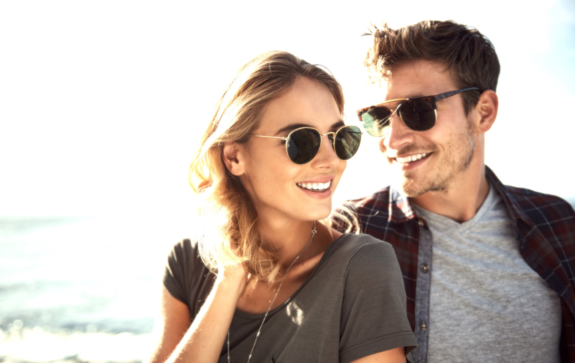 A man and woman smile while wearing sunglasses.