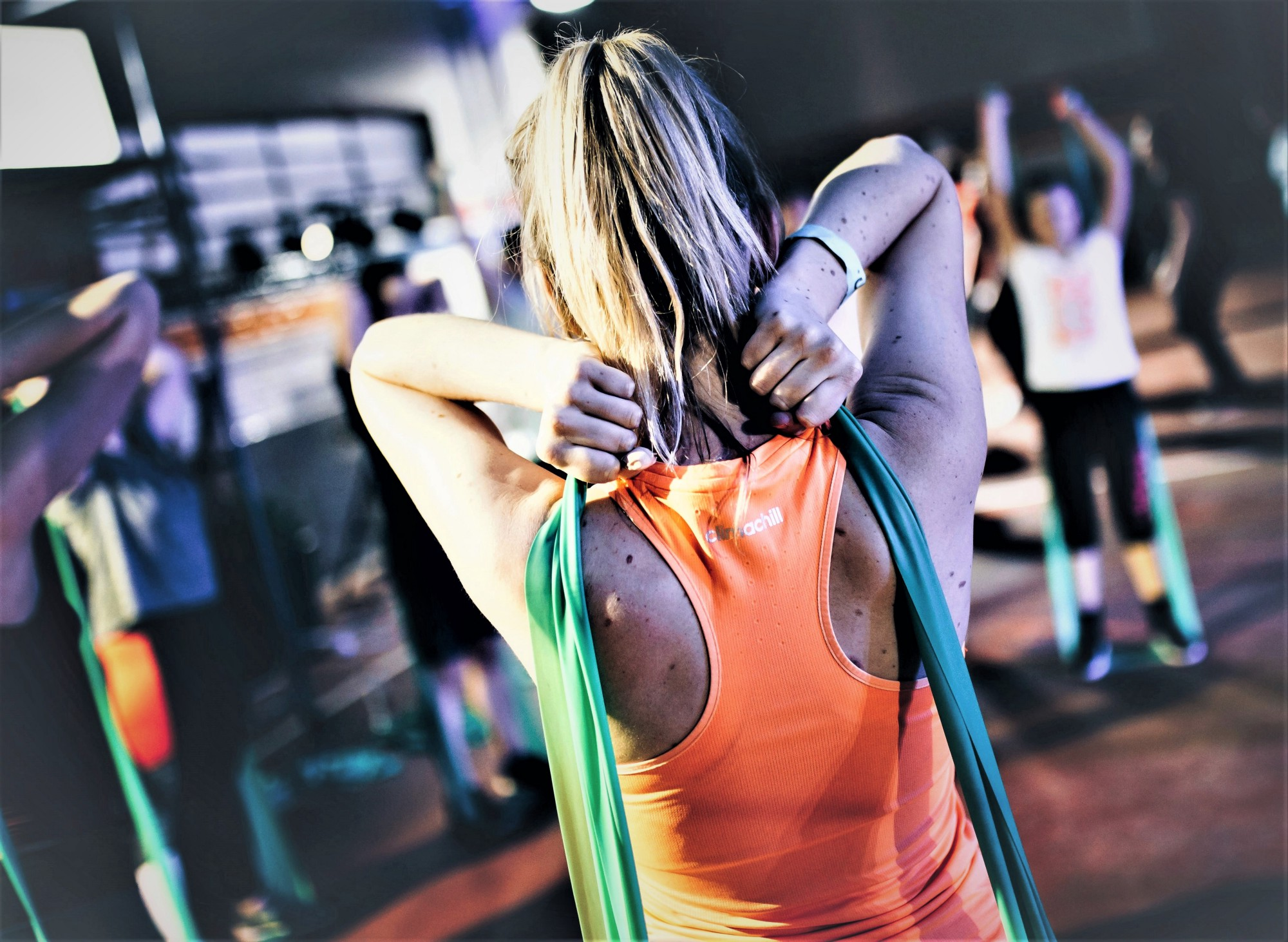 girl with blonde hair in ponytail wearing sleeveless orange top working out at gym with stretch bands