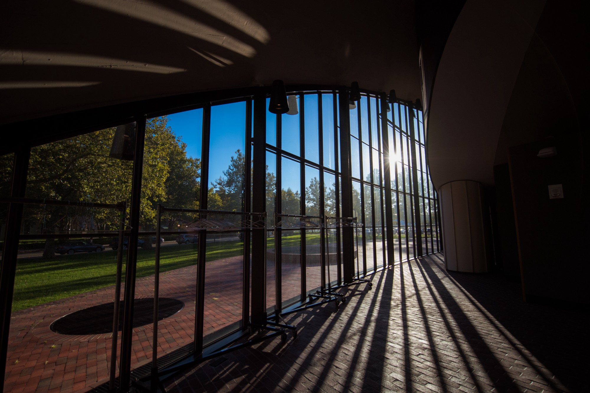 View from inside the Kresge auditorium of the sun shining and casting shadows on the ground in the foyer