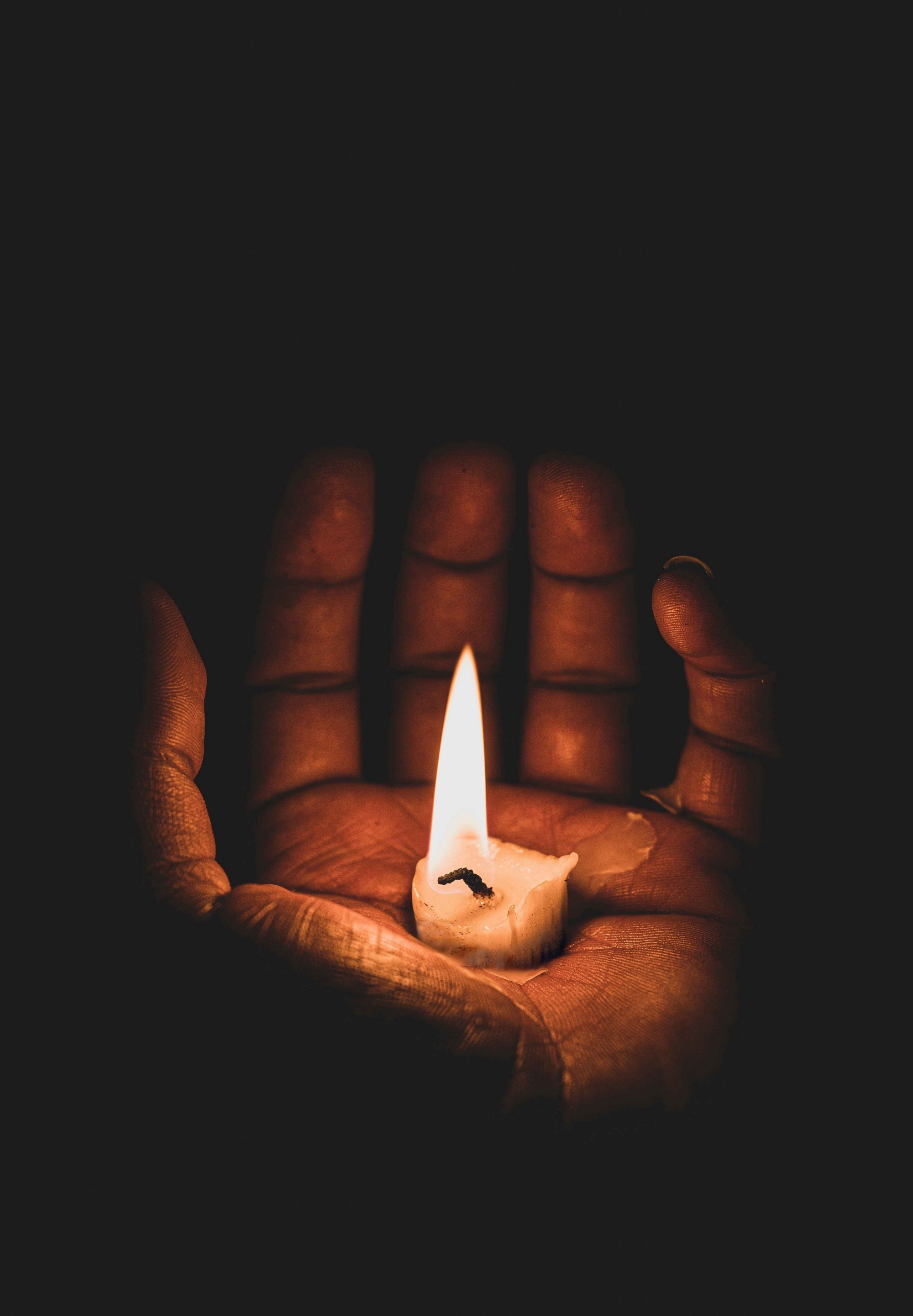 Nearly burned-out candle held on a person's open palm.