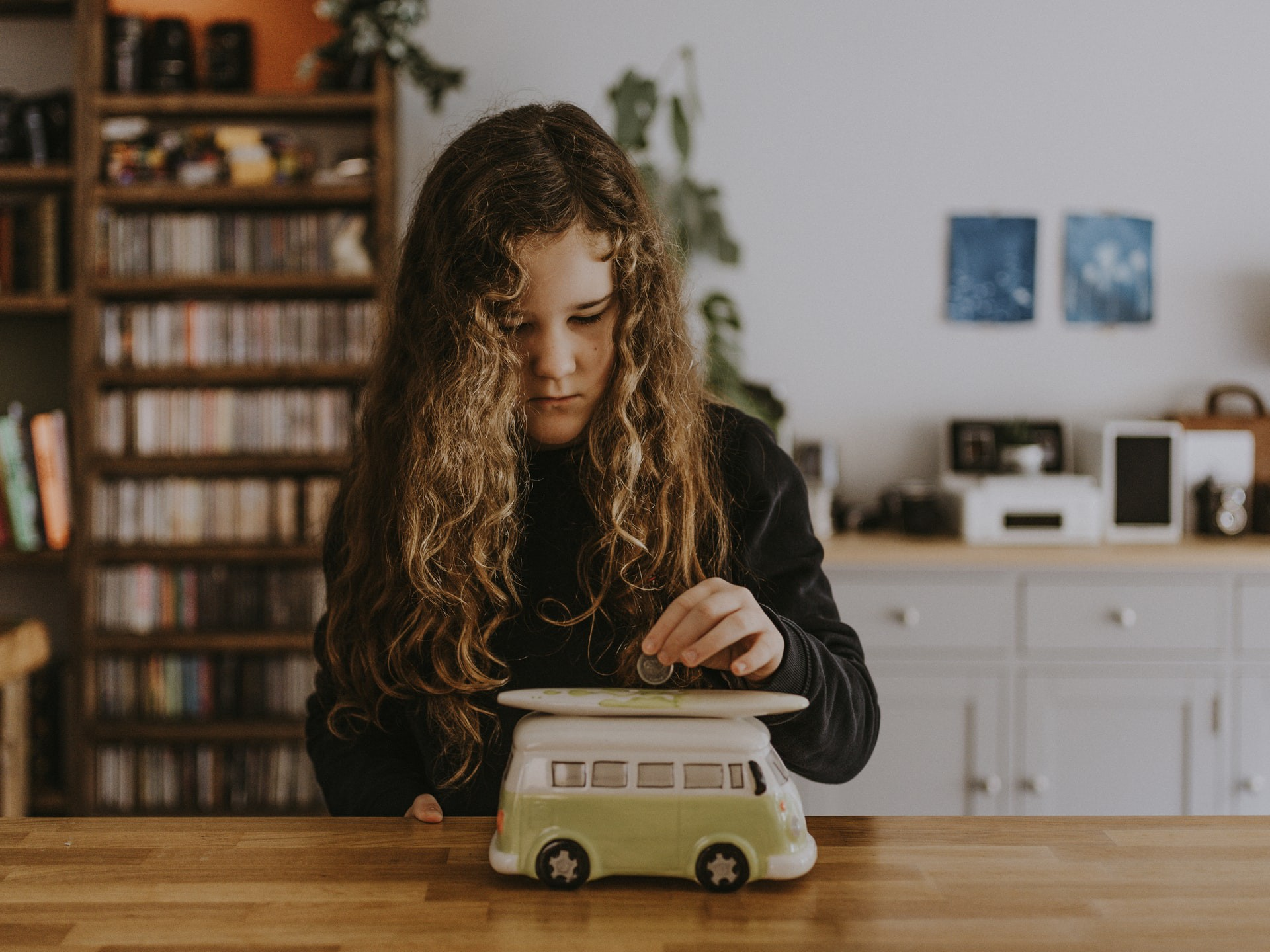 Young lady inserting a coin into a coin container shaped like a bus.