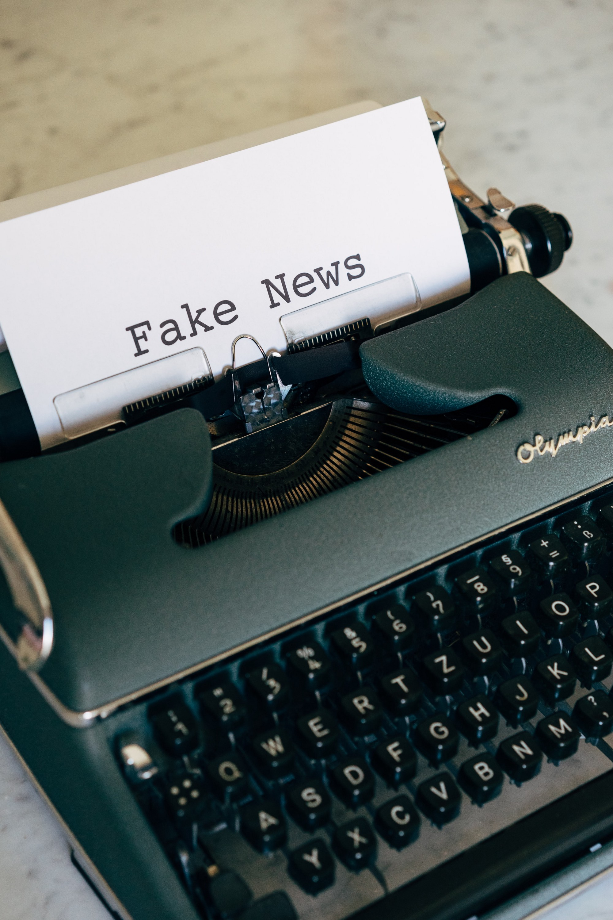 """A typewriter with the words """"fake news"""" typed on the page"""