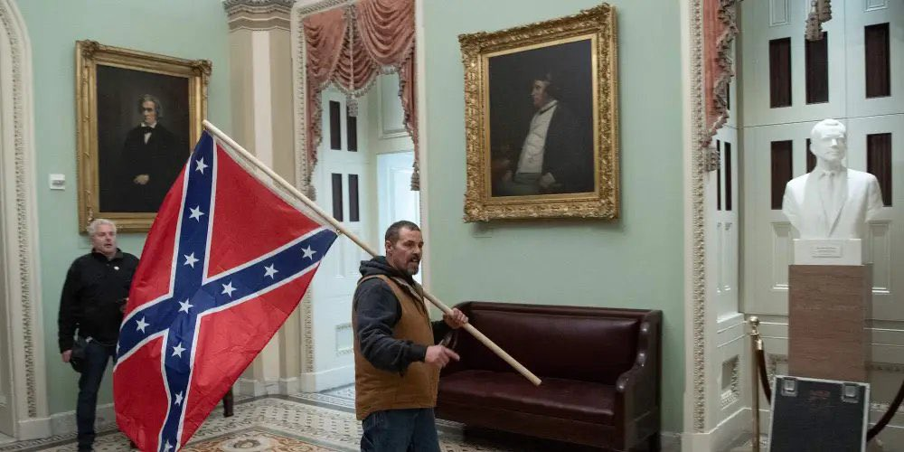 Rioter carries Confederate battle flag in halls of U.S. Congress during January 6 insurrection.