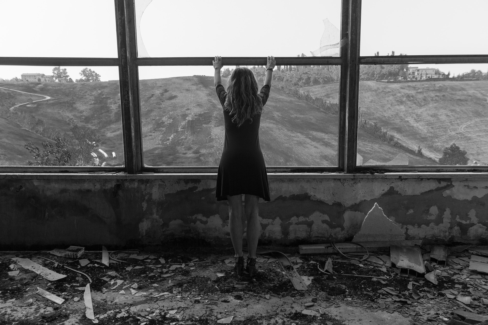 Girl in abandoned building looking at desolate landscape.