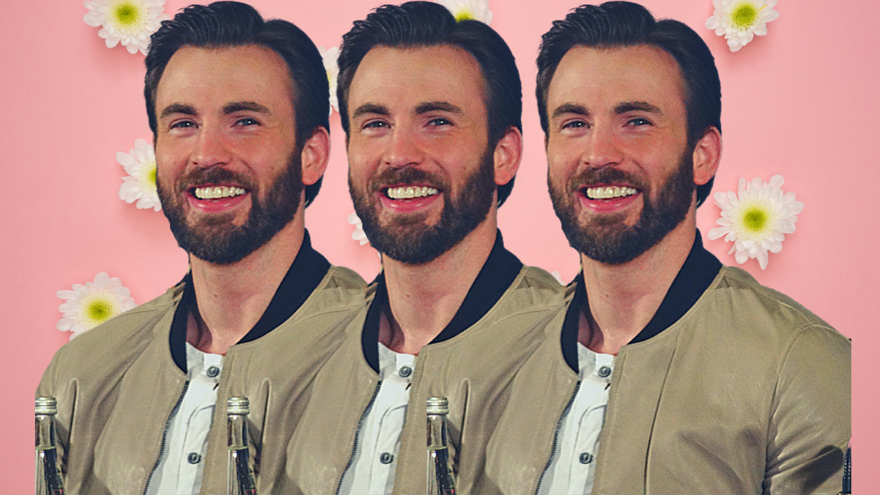 Chris Evans on a pink background with flowers. He is smiling at the camera wearing a tan bomber jacket.