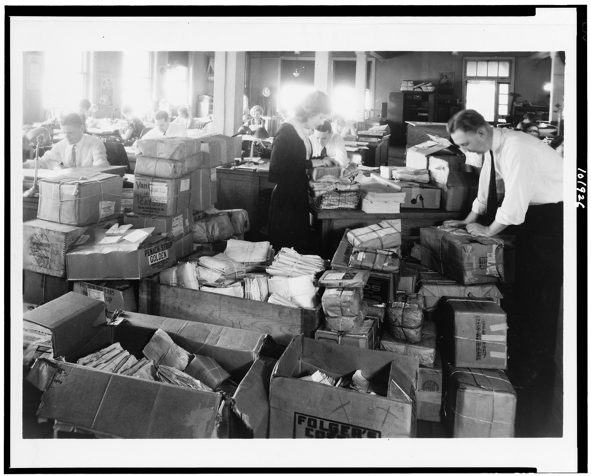 Office workers handling boxes of mail and paperwork.