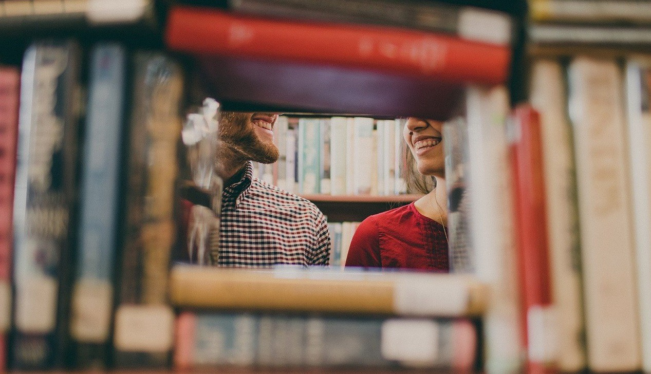 The view is of a library where a space between books shows a man and woman smiling at each other