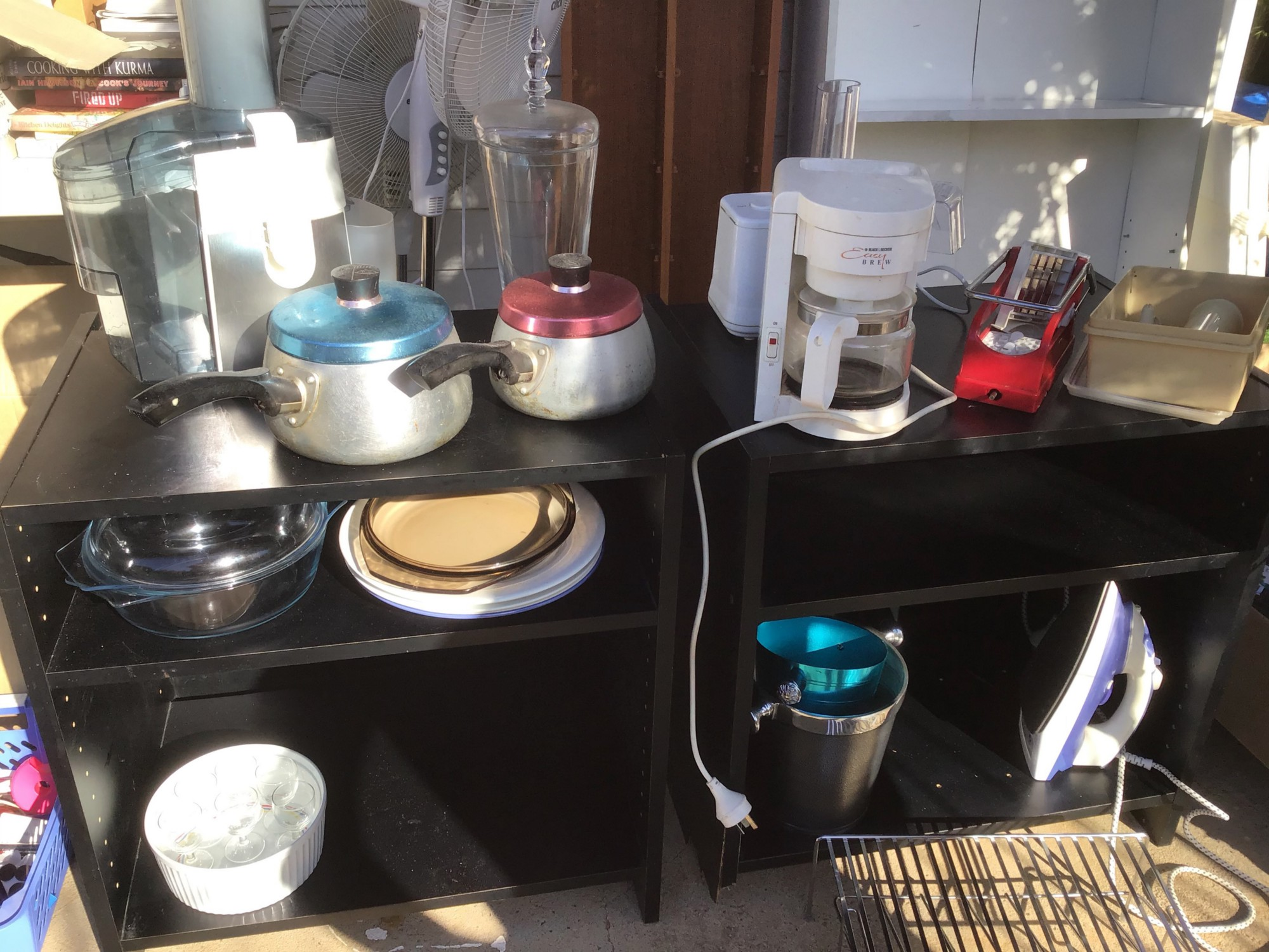 A close up shot of two small black side tables with household items such as saucepans, a coffee maker, a juicer, and iron, some baking ware. All this is on a front porch, ready to give away.