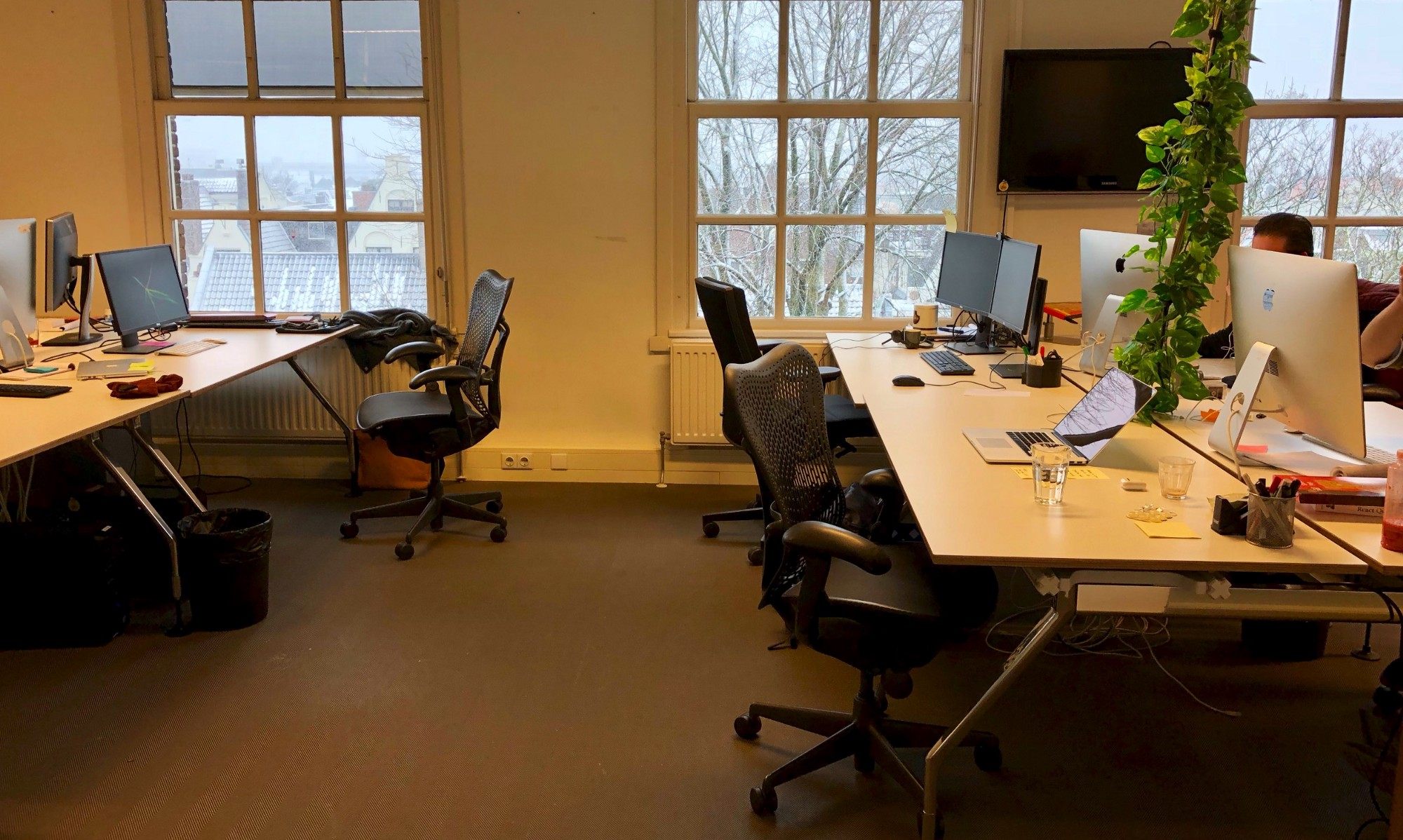 Four empty desks in an office building during winter