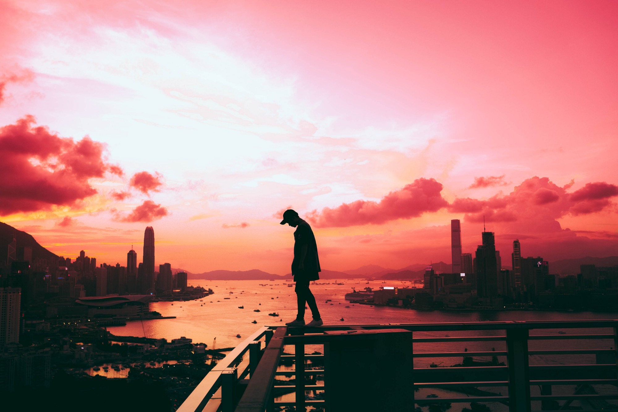 Man standing on edge of building in Hong Kong.