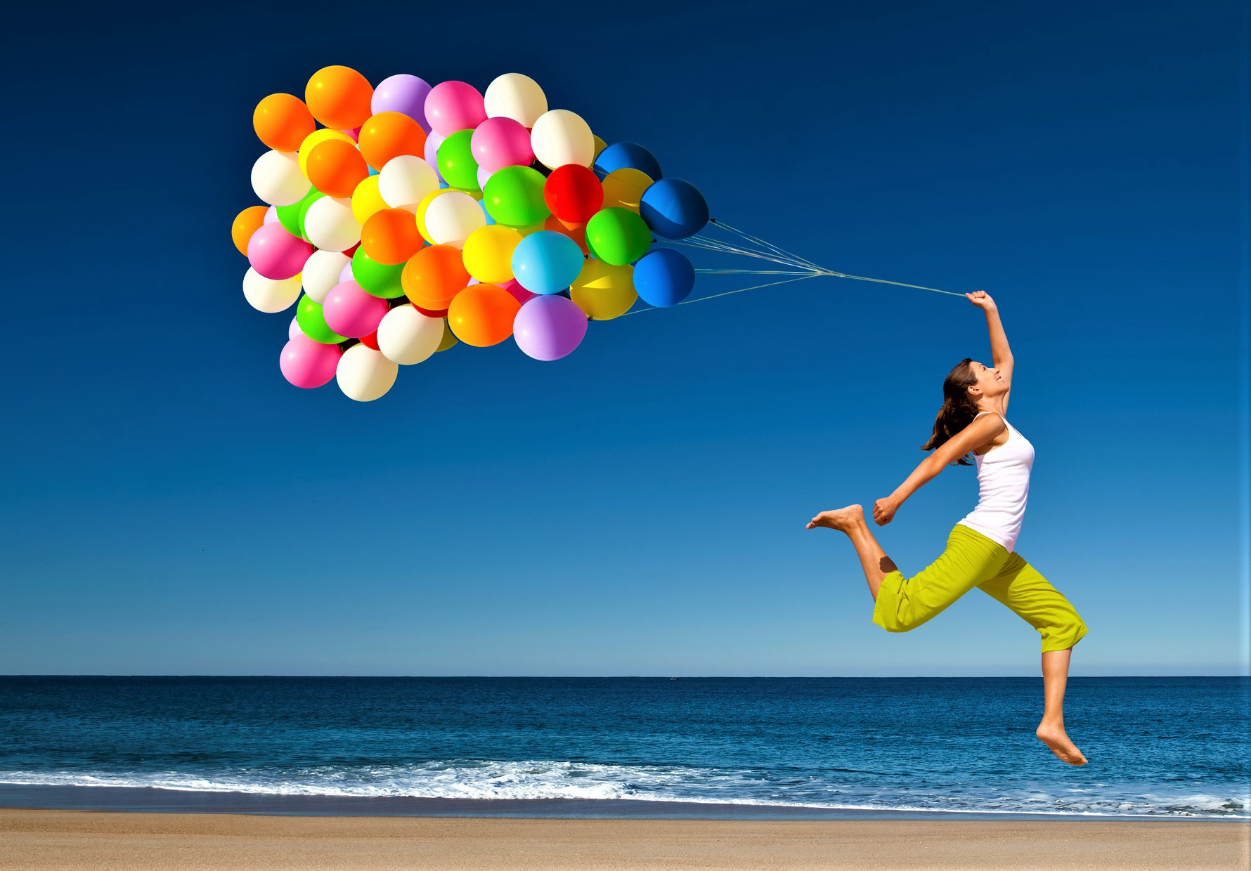 Woman with dark hair wearing sleeveless white shirt and bright green pants leaping in air hold large group of colorful balloons