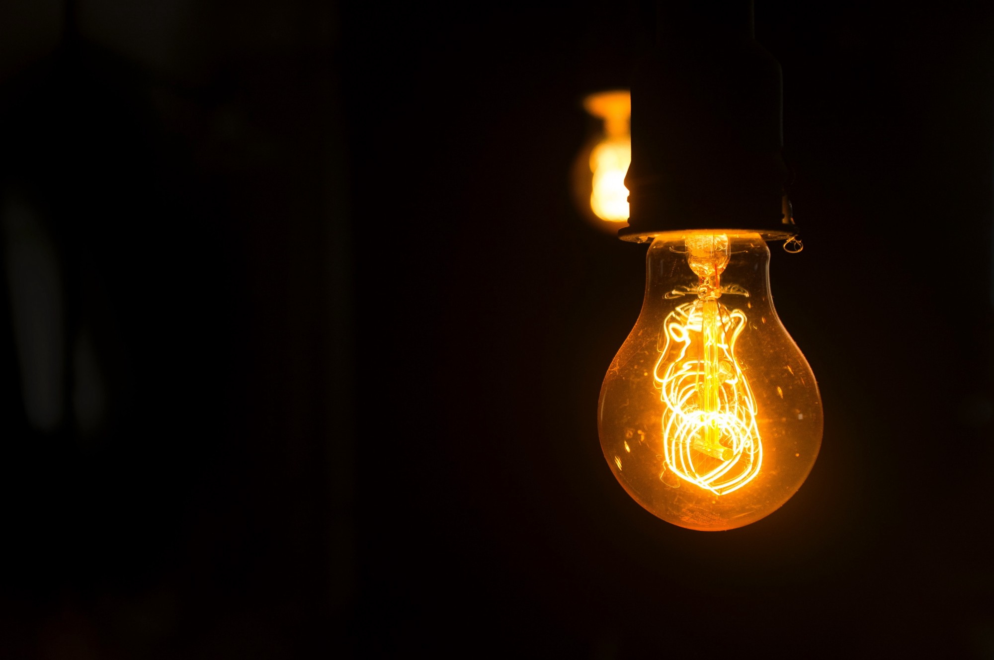 Yellow lightbulb with delicate glowing filaments.