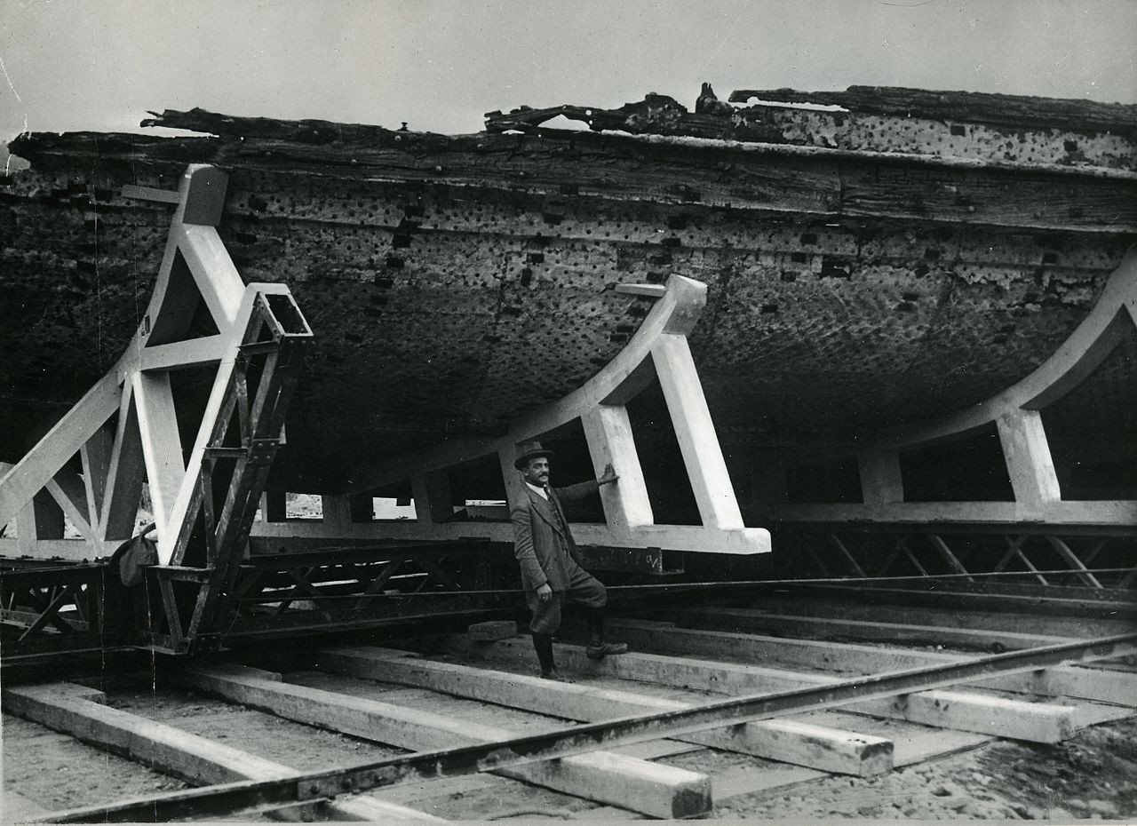 Black and white photograph of a man standing in front of a giant wooden hull