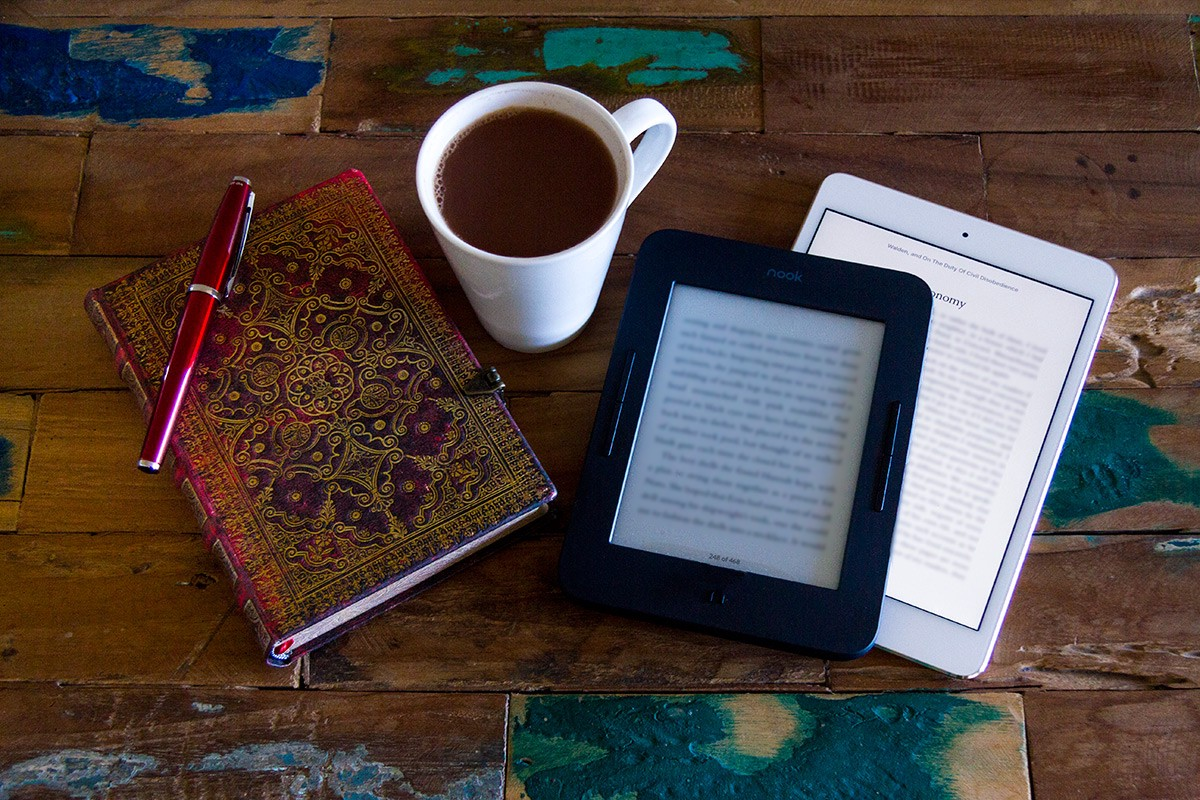 An ebook reader, iPad, a notebook and pen, and a cup of hot chocolate all on a rough wooden table.
