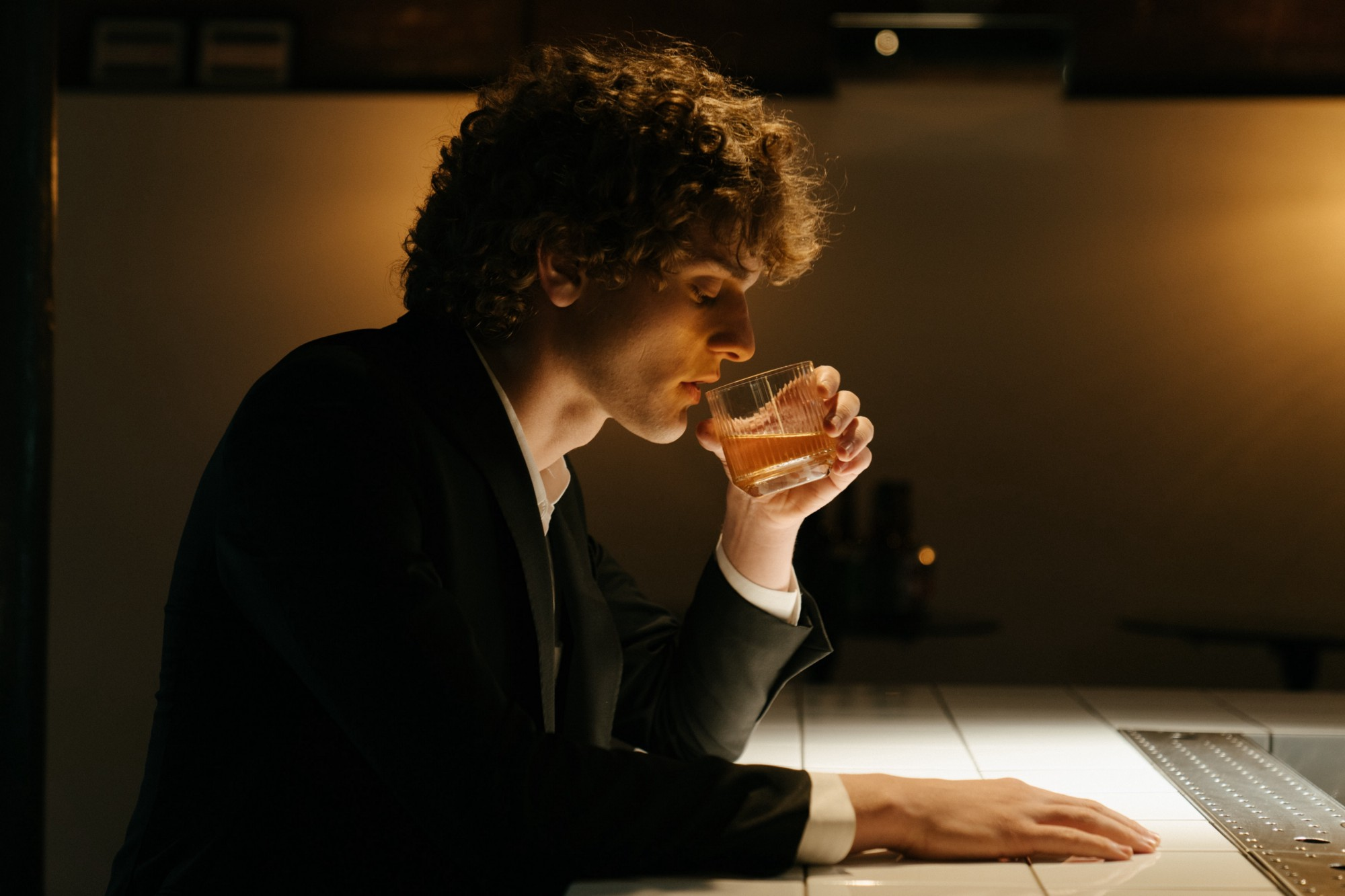 Single man drinking alone at the bar of a restaurant.