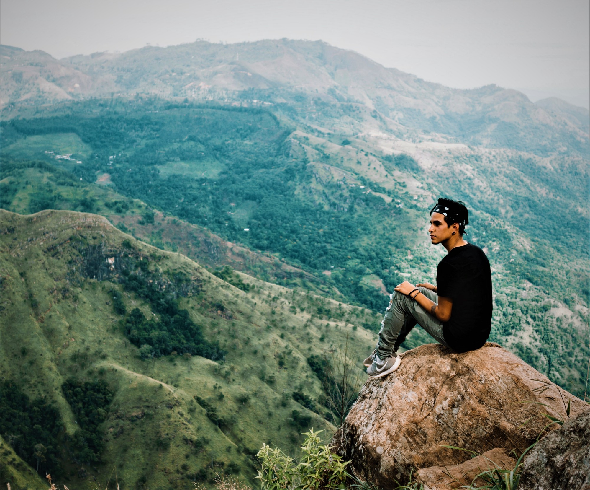 young man sitting on boulder looking to the side backdrop of green hills behind him