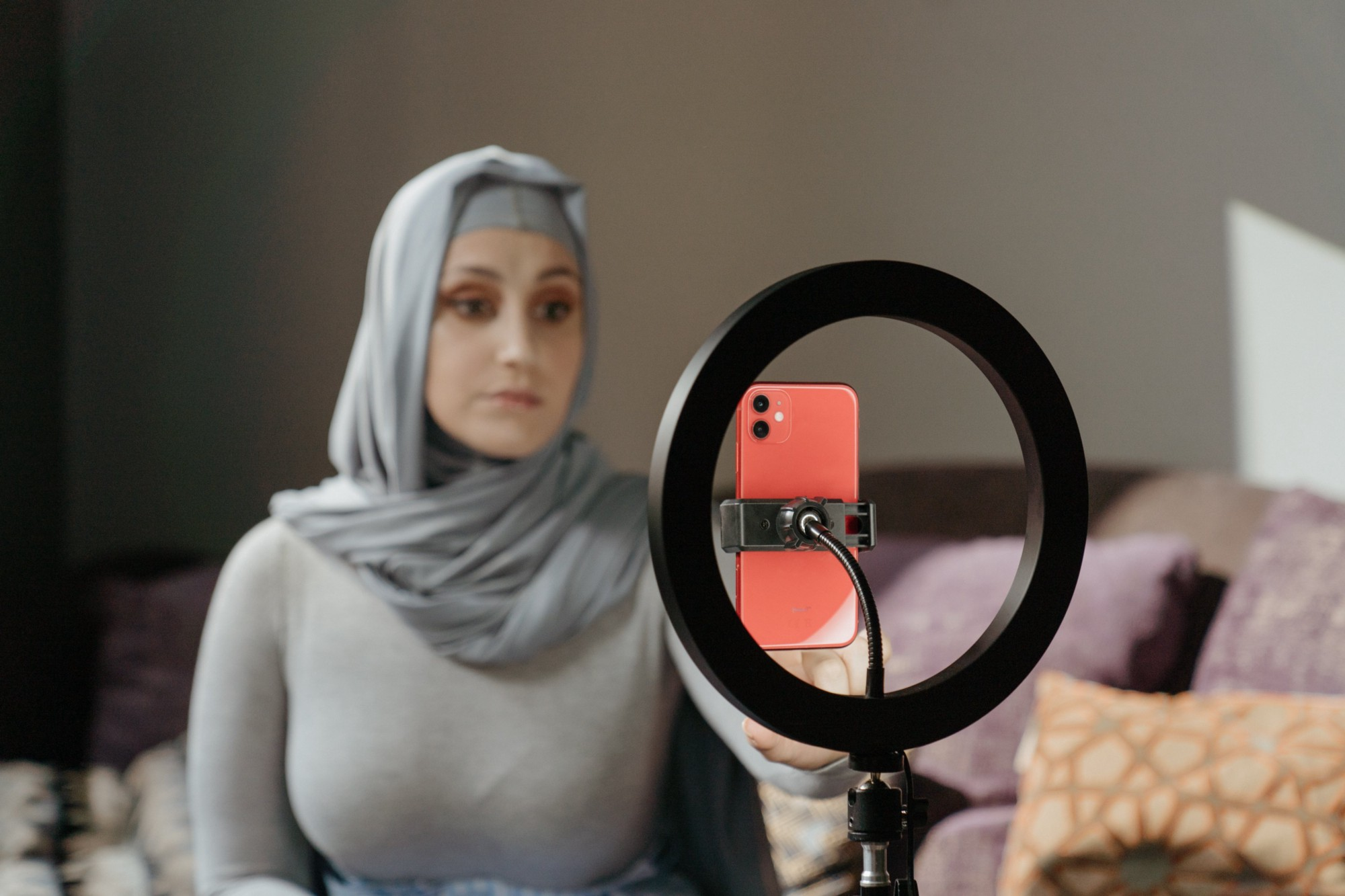 A woman in a grey blouse and grey hijab sitting in front of a ring light holding a coral-colored mobile phone.