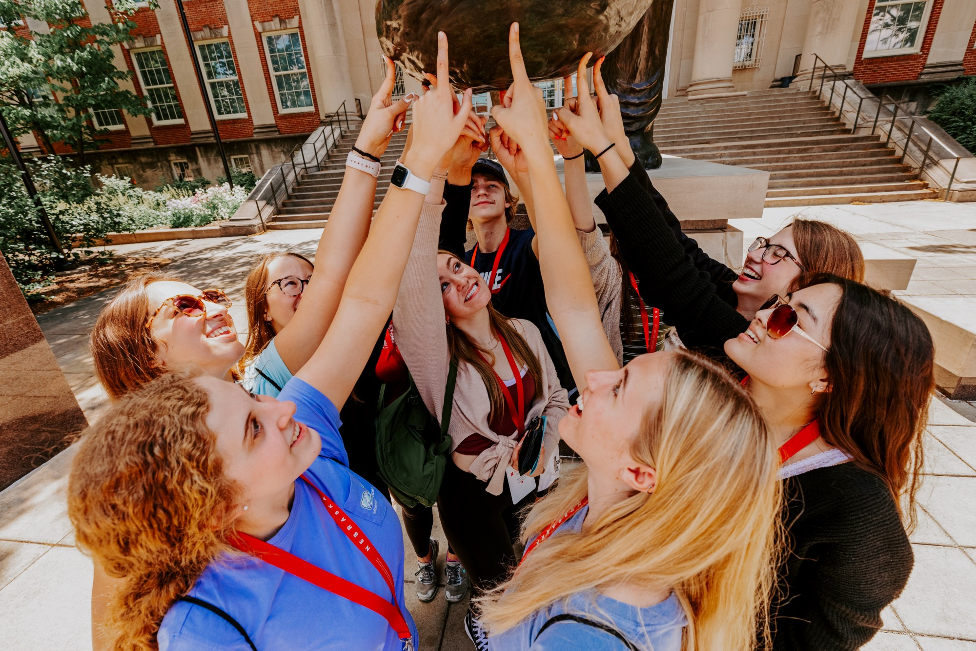 A group of new Huskers touches Archie the mammoth's paw for good luck outside of Morrill Hall.