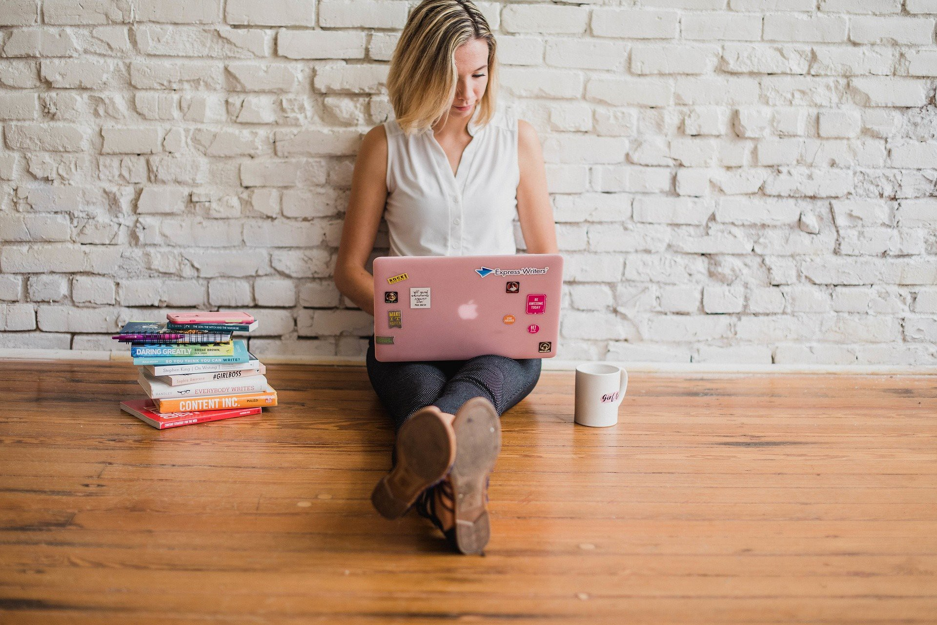 Woman typing on a laptop against a brick wall. An Open Letter to New Writers Who Want to Succeed.