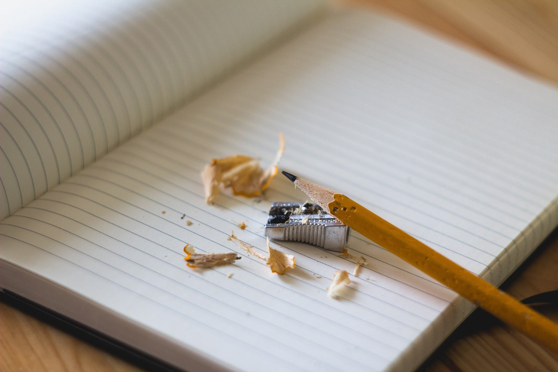 A blank notebook with a pencil and sharpener.