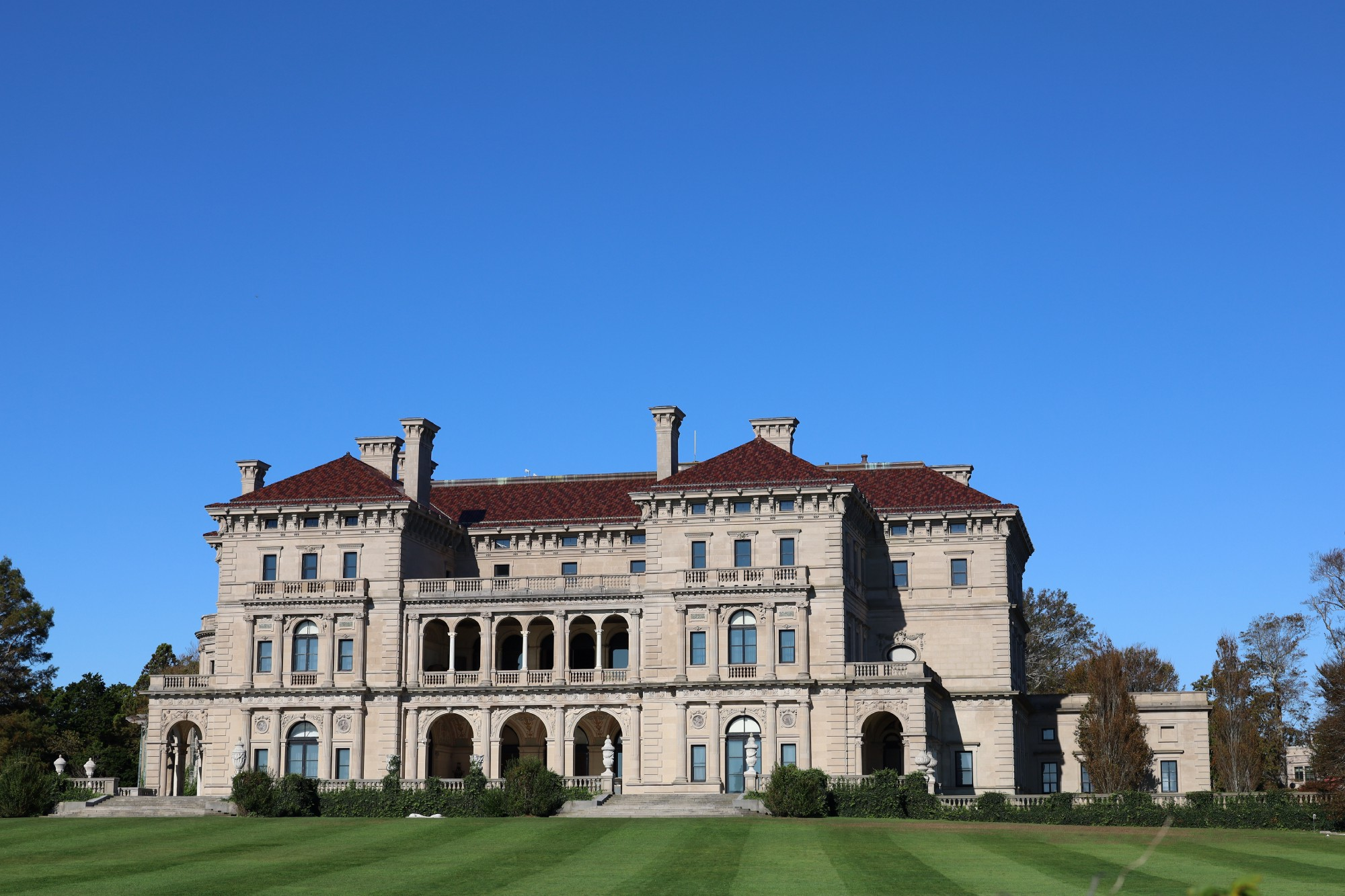 """Massive mansion from the so-called """"Guilded Age"""" with a perfectly manicured lawn in front and a cloudless blue sky above."""