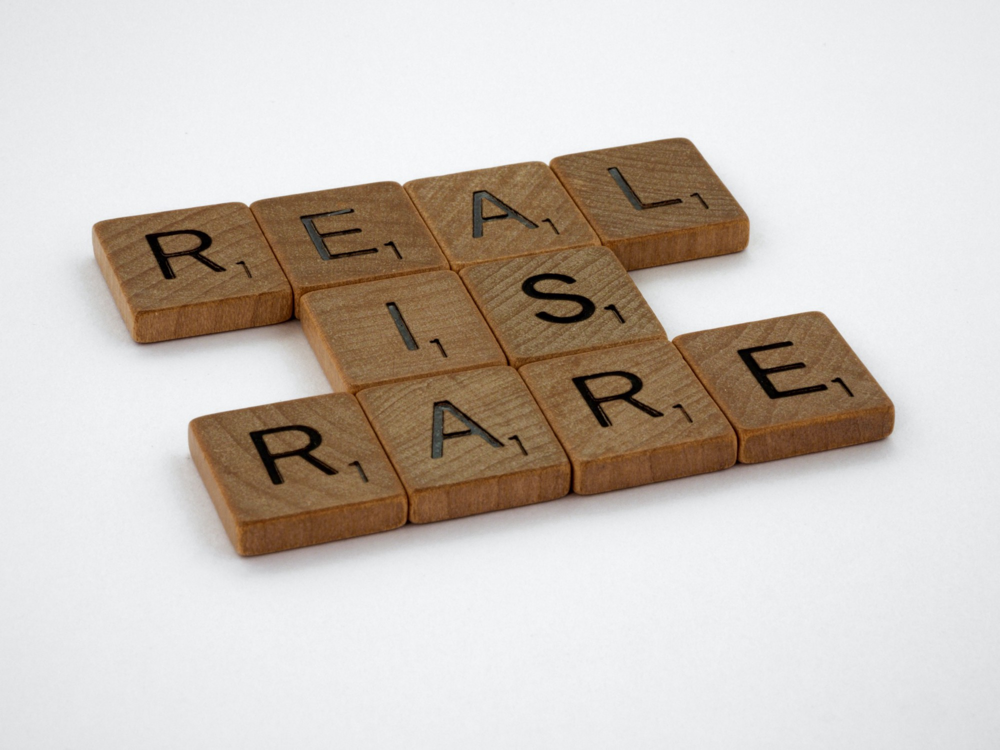 brown Scrabble tiles spelling out 'real is rare'
