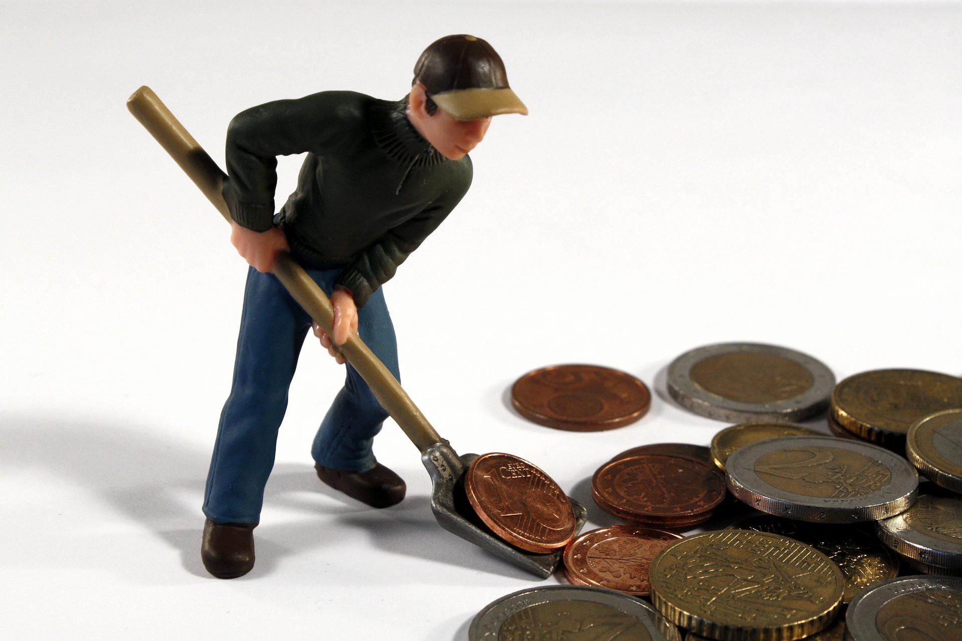 Toy figure of a man shoveling coins.
