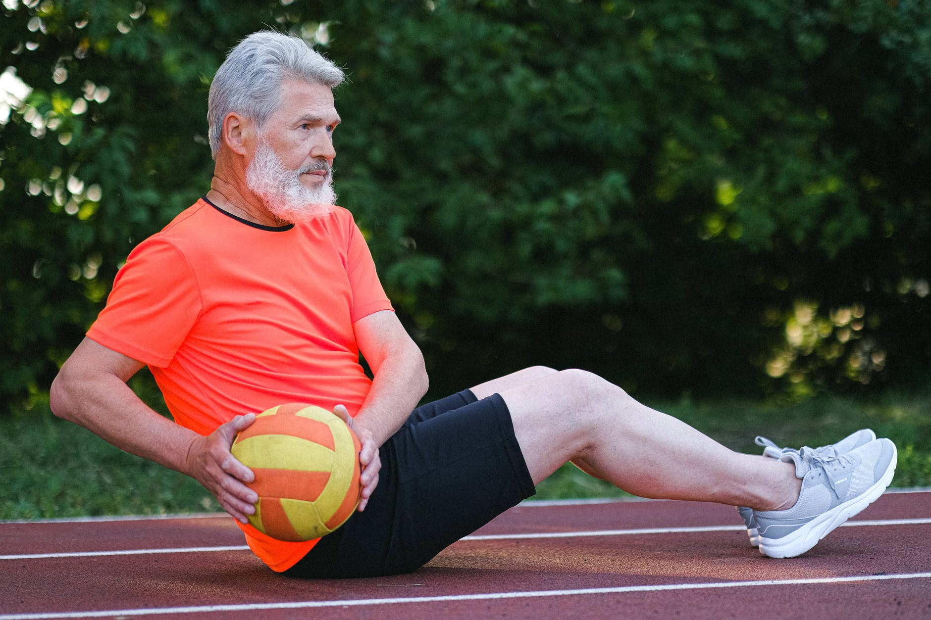 Old man aging gracefully as he performs russian twists