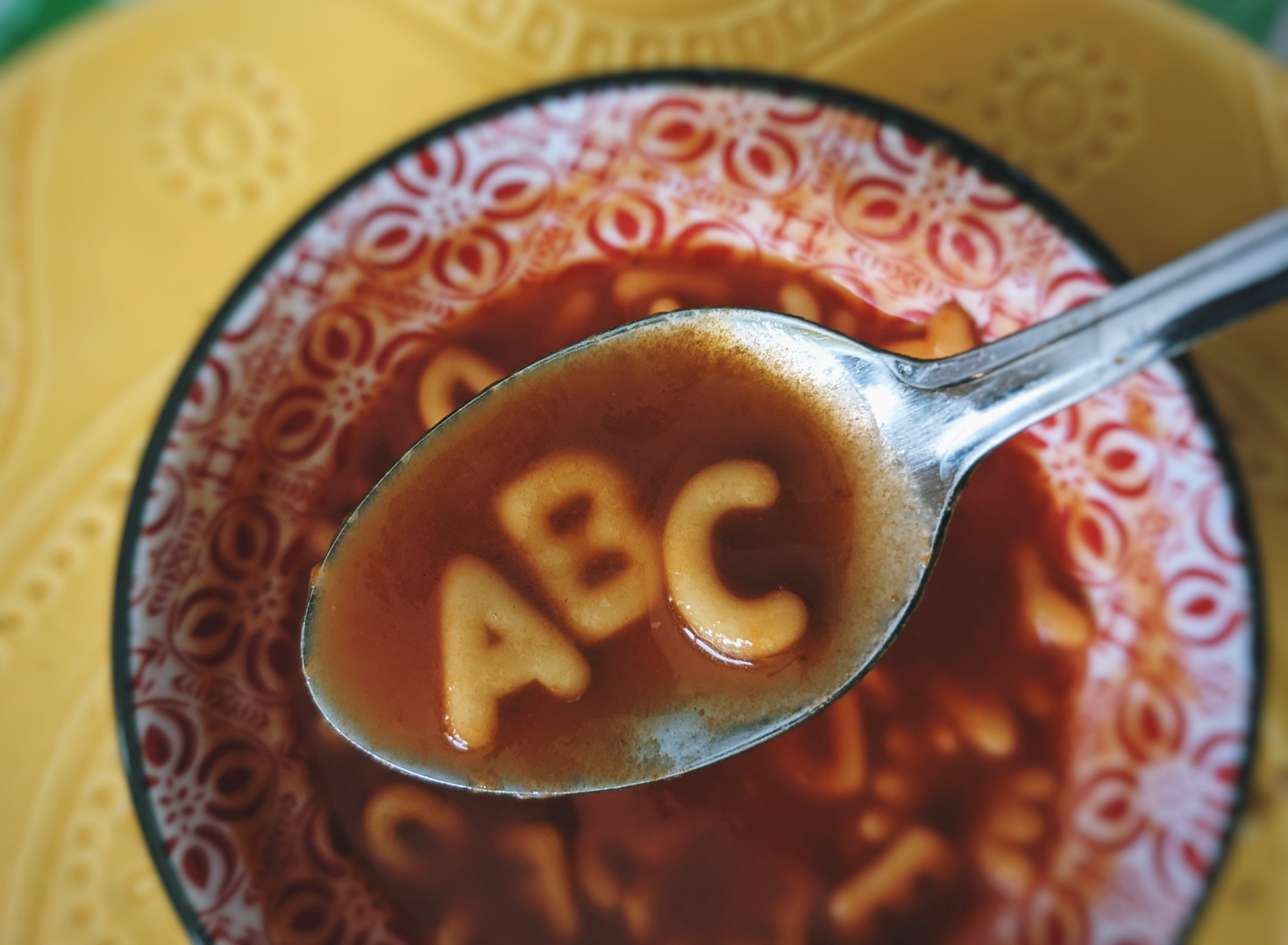 Closeup of spoon with ABC noodles above red-patterned bowl of alphabet soup o yellow tablecloth.