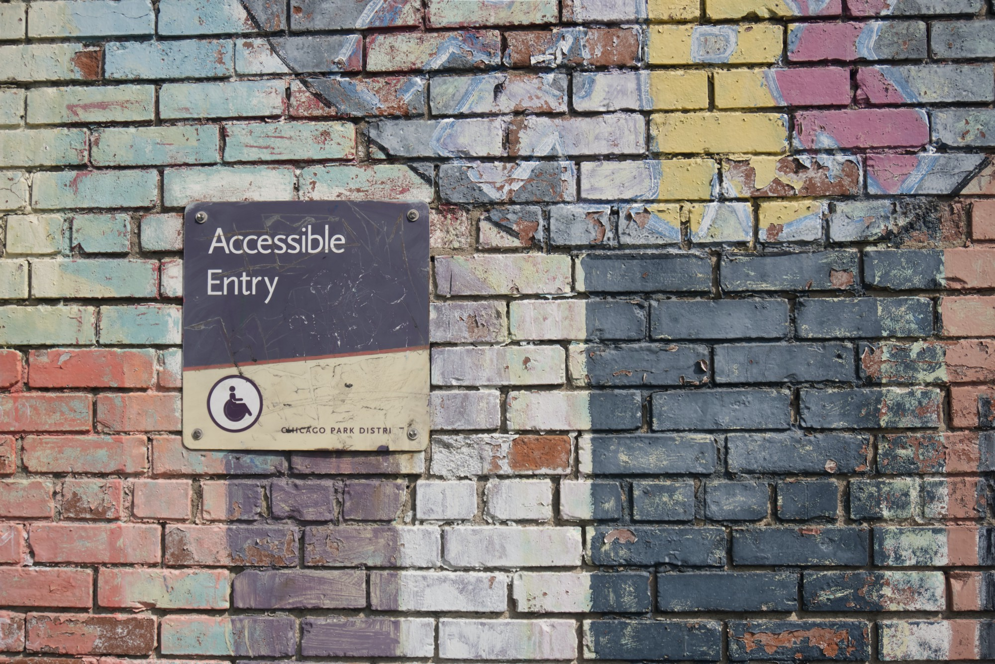 """A sign on a painted brick wall reading """"Accessible Entry"""""""