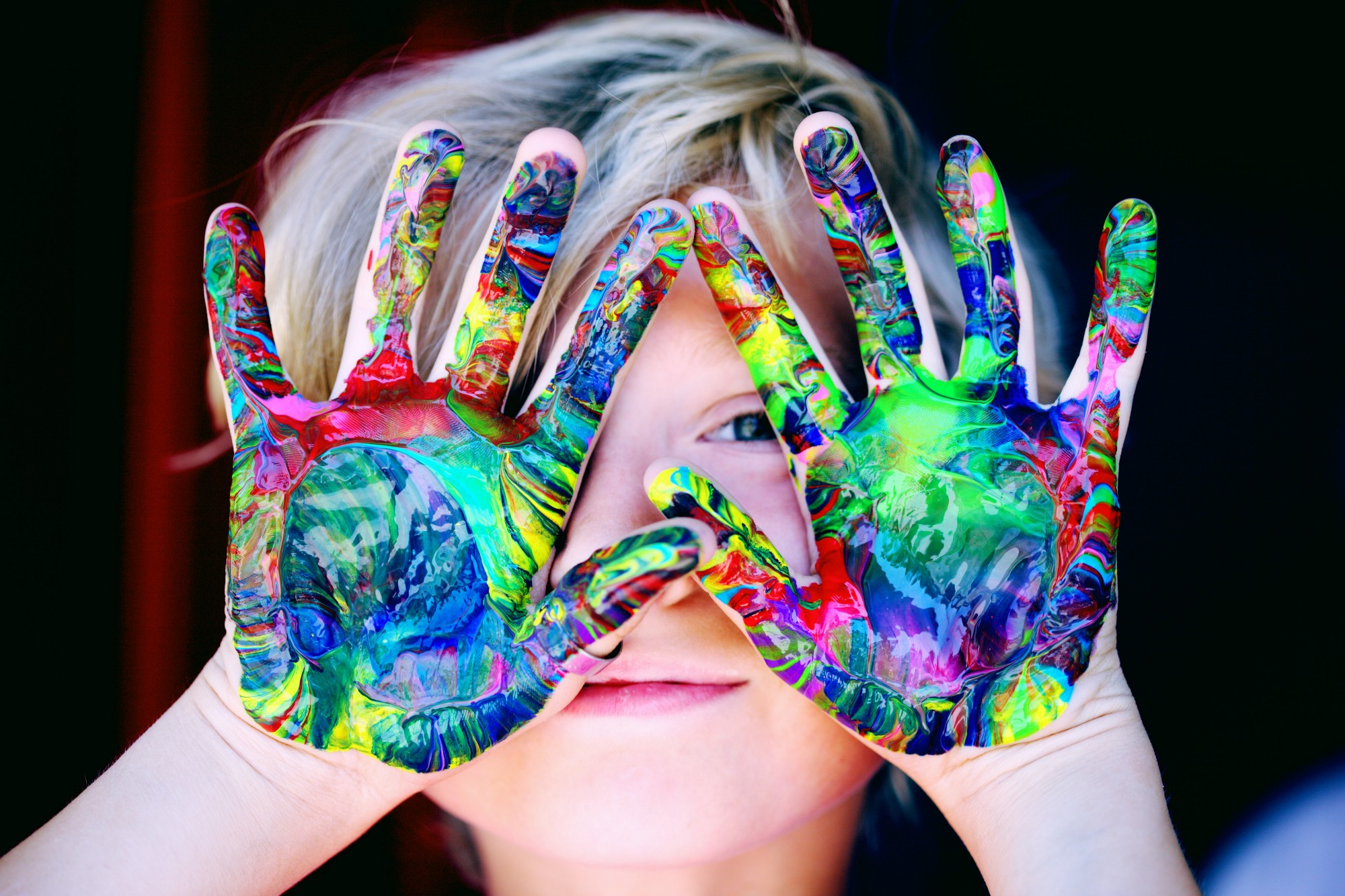 Image of a boy with colors in his hand.